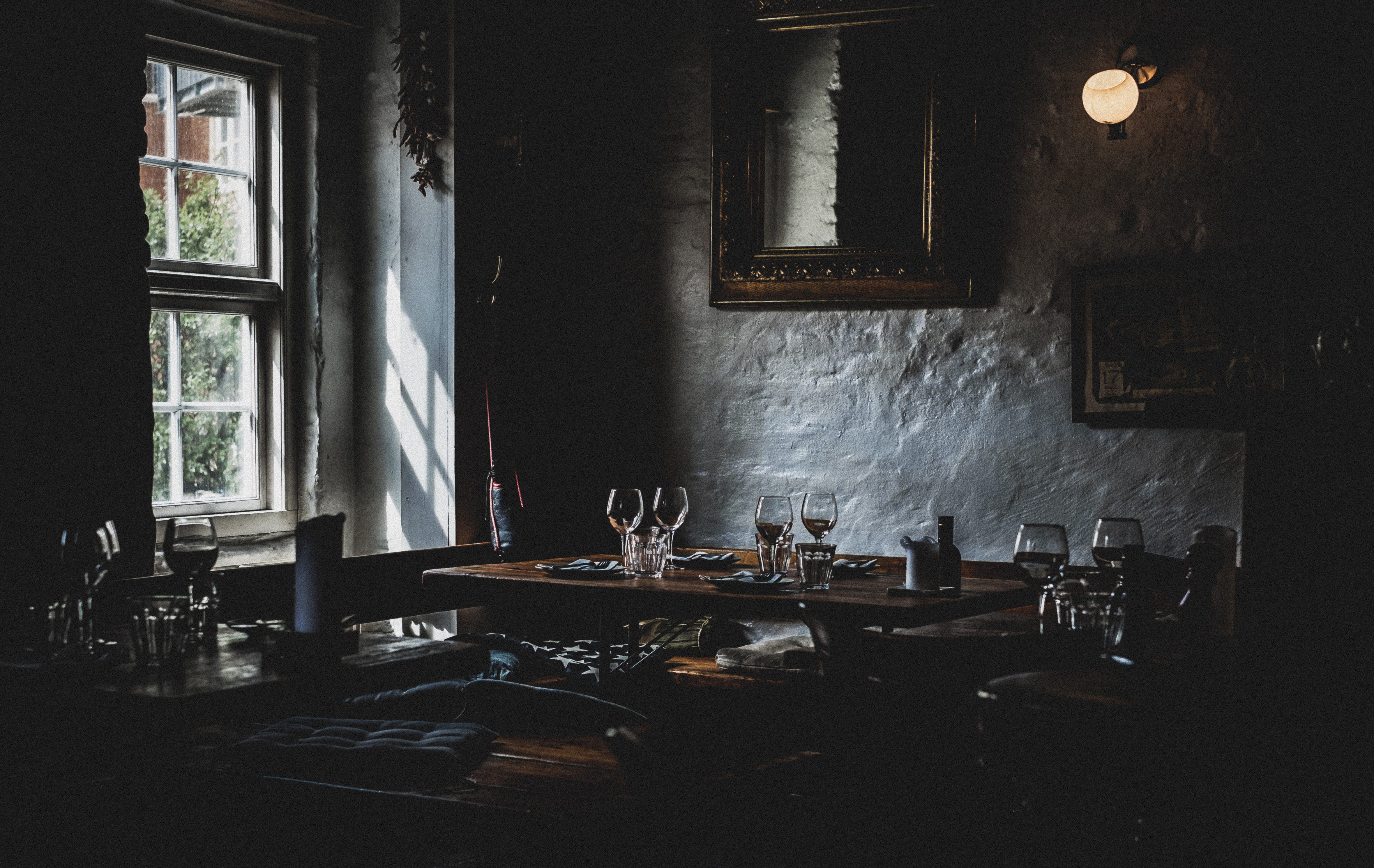 A table with plates and wine glasses in a corner of a dark restaurant room