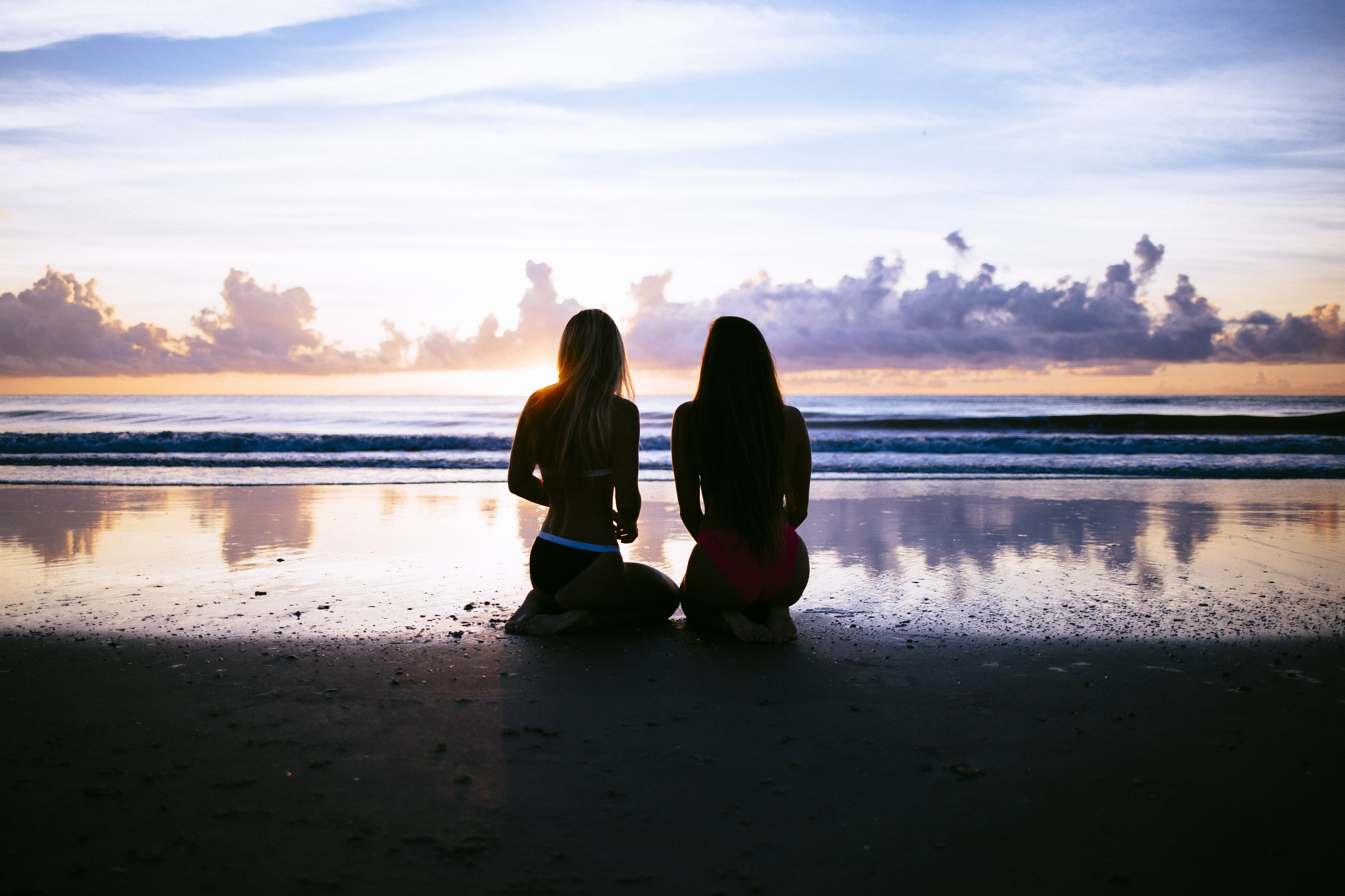 A dim shot of two women in bikini kneeling on a wet beach and admiring the sunset