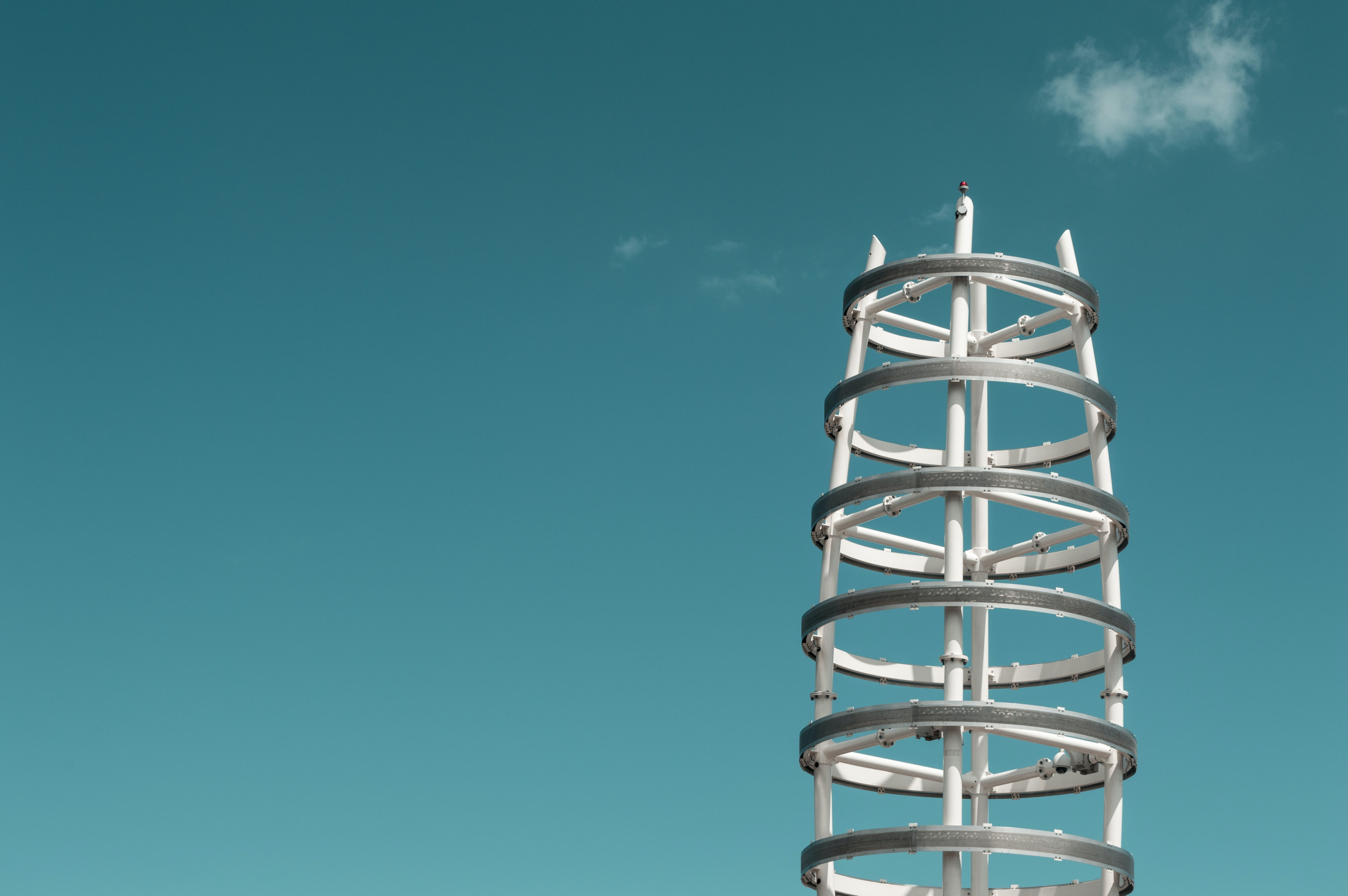 A white steel structure with gray rings against an azure sky