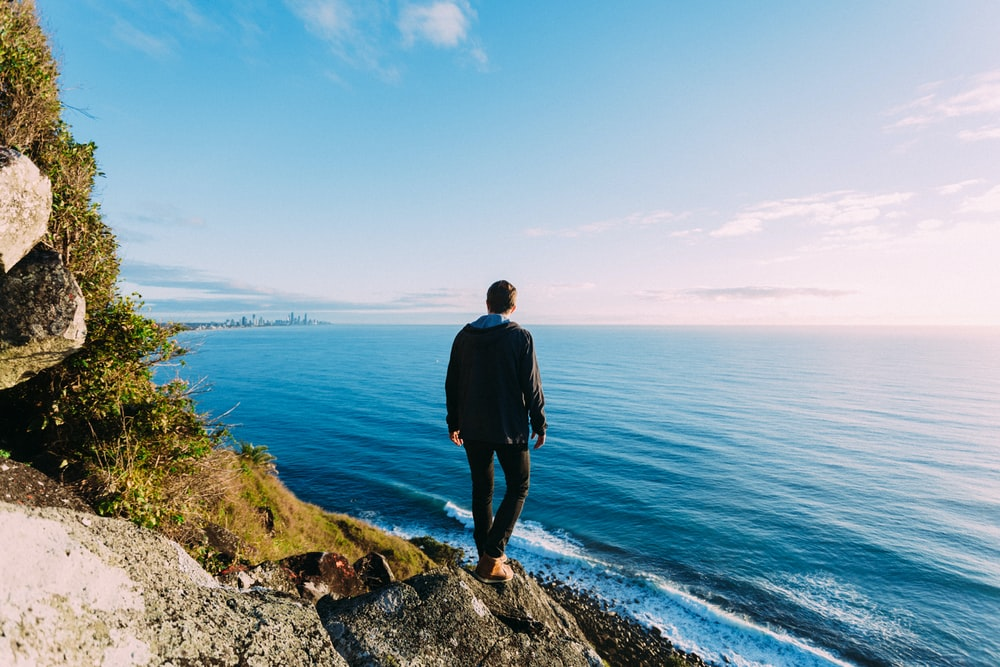 man standing on rock cliff near sea