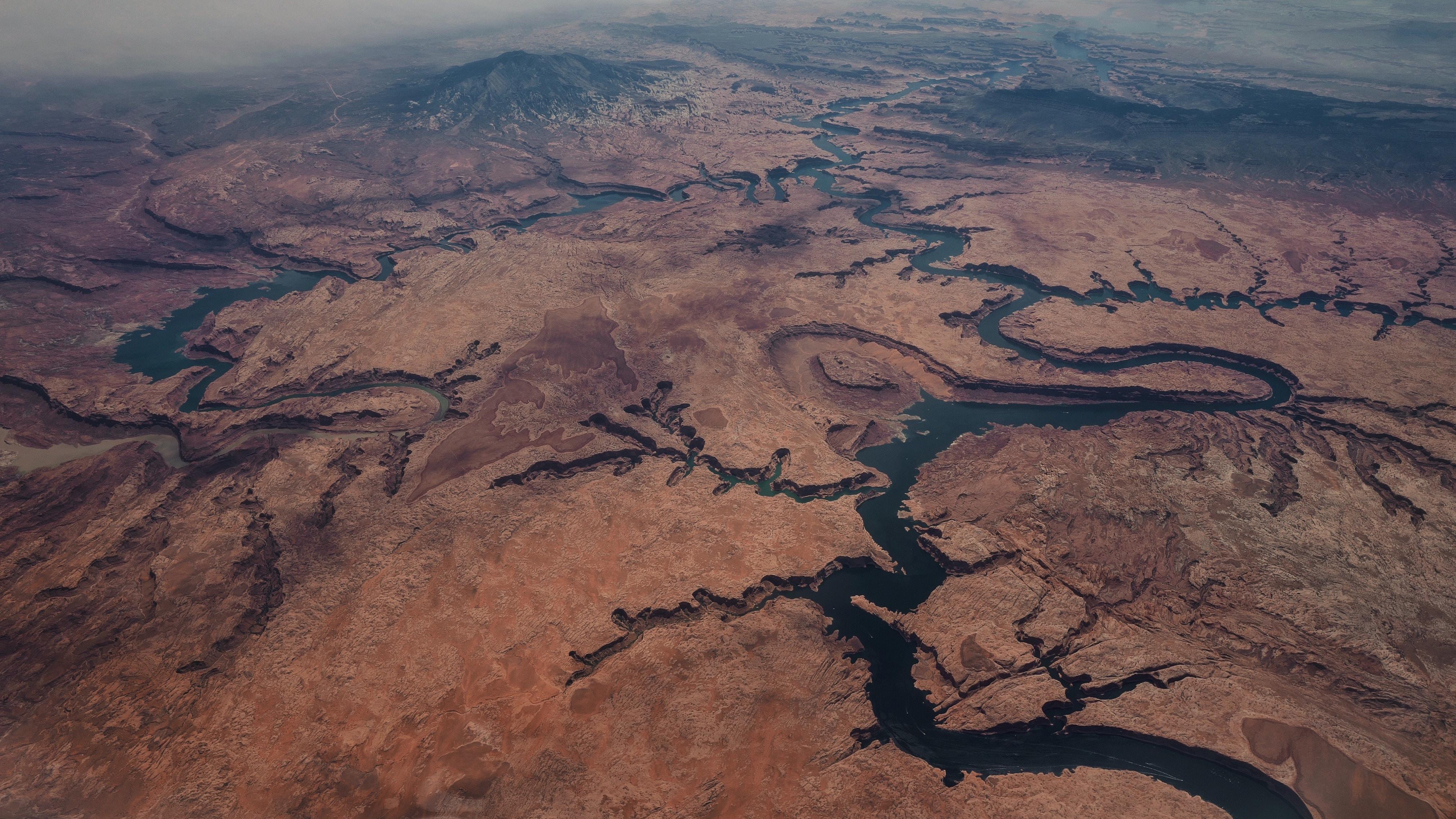 Aerial drone shot of dark rivers winding in desert terrain