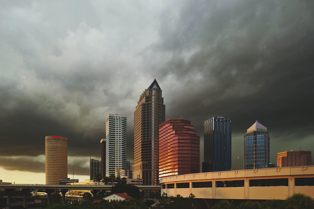 wide angle photo of buildings under cumulus clouds