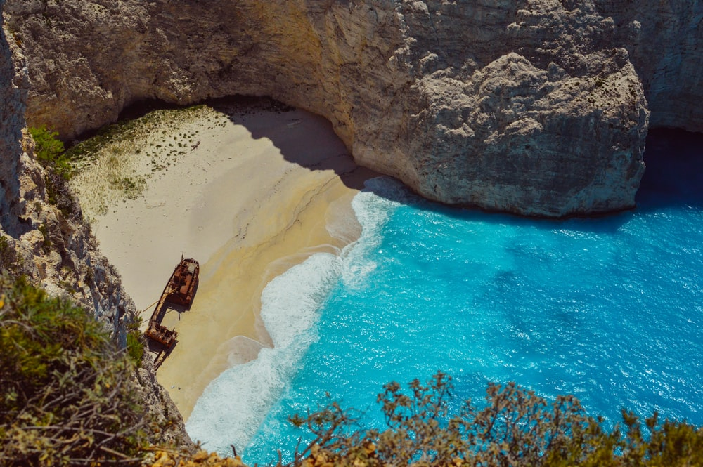 wrecked ship on shore near cliff during daytime