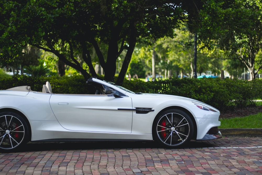 white Aston Martin convertible parked near trees