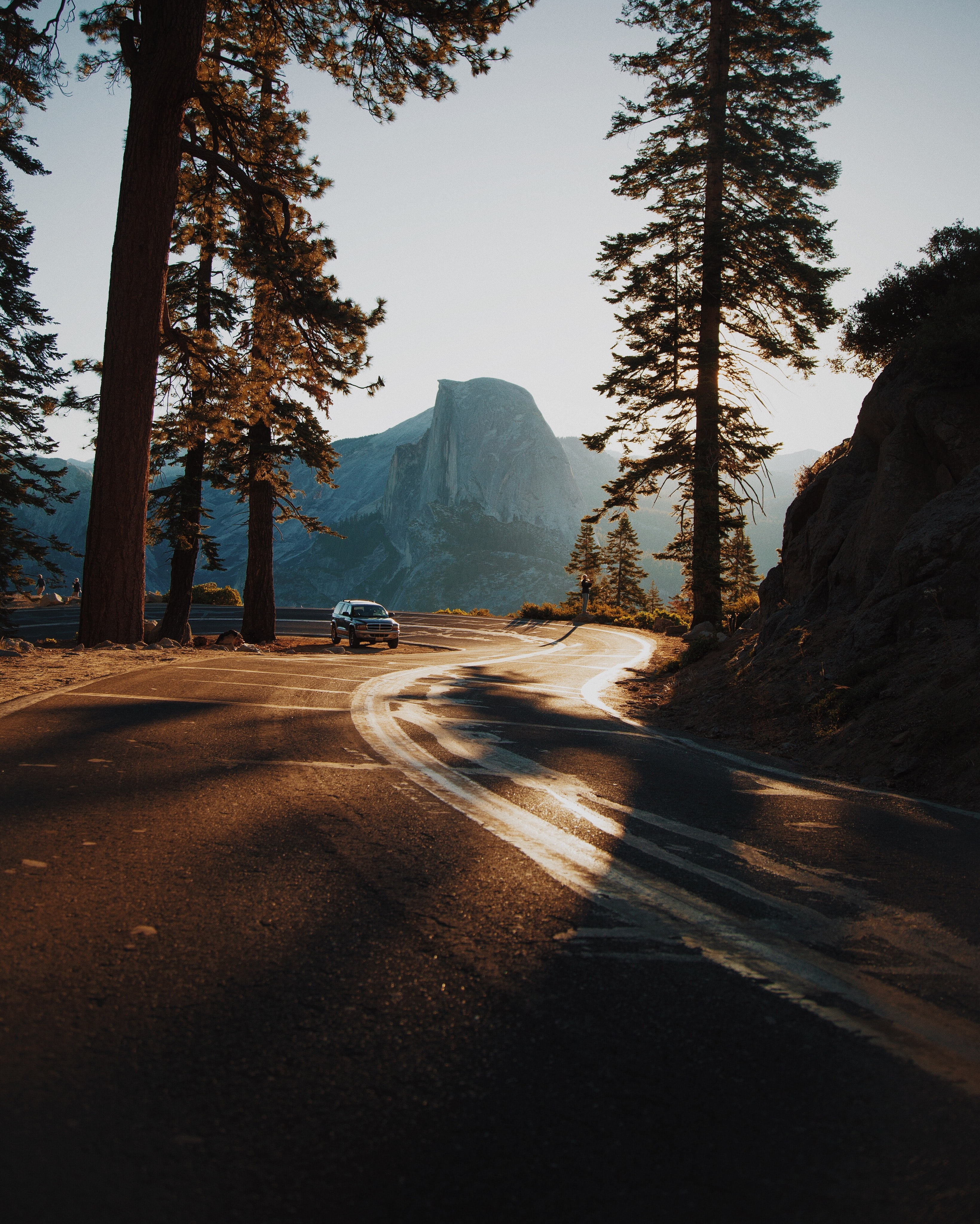 An SUV driving on a curve in a mountain road in sunlight