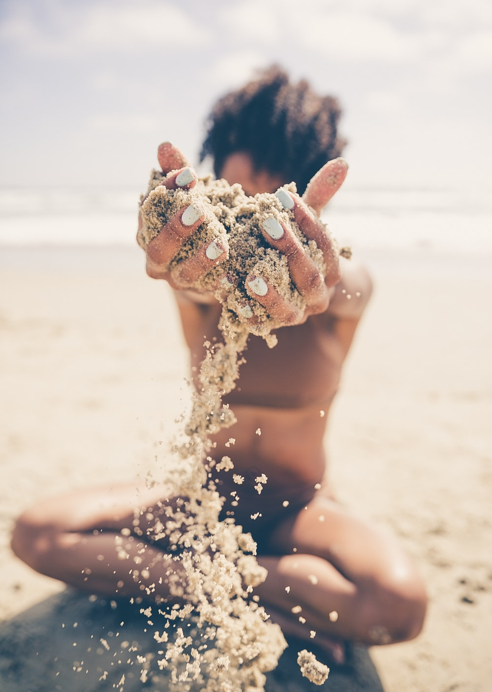 selective focus photo of woman sitting and raising sand during daytime