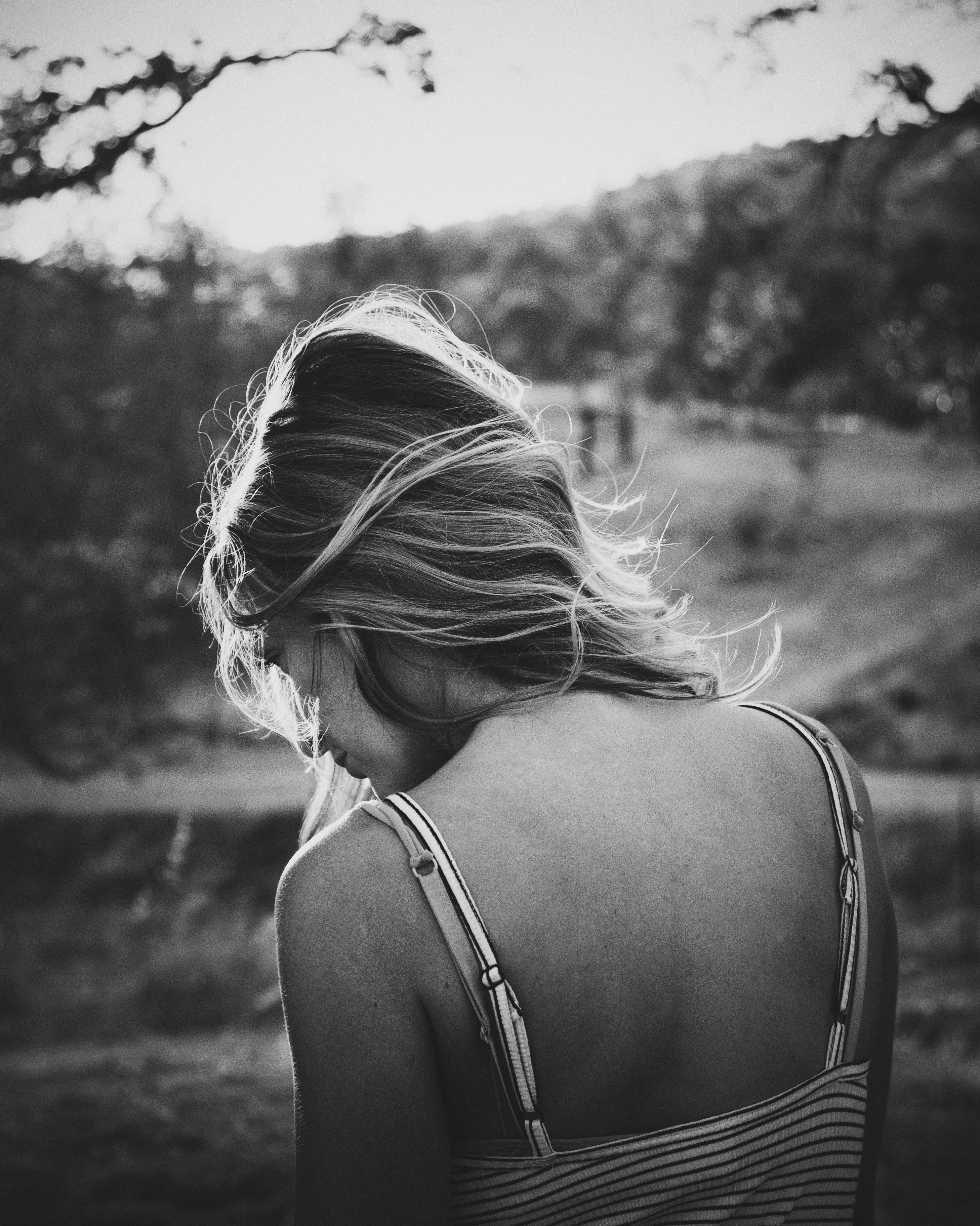 Shot of young woman with windswept hair from behind wearing vest top in park with nature