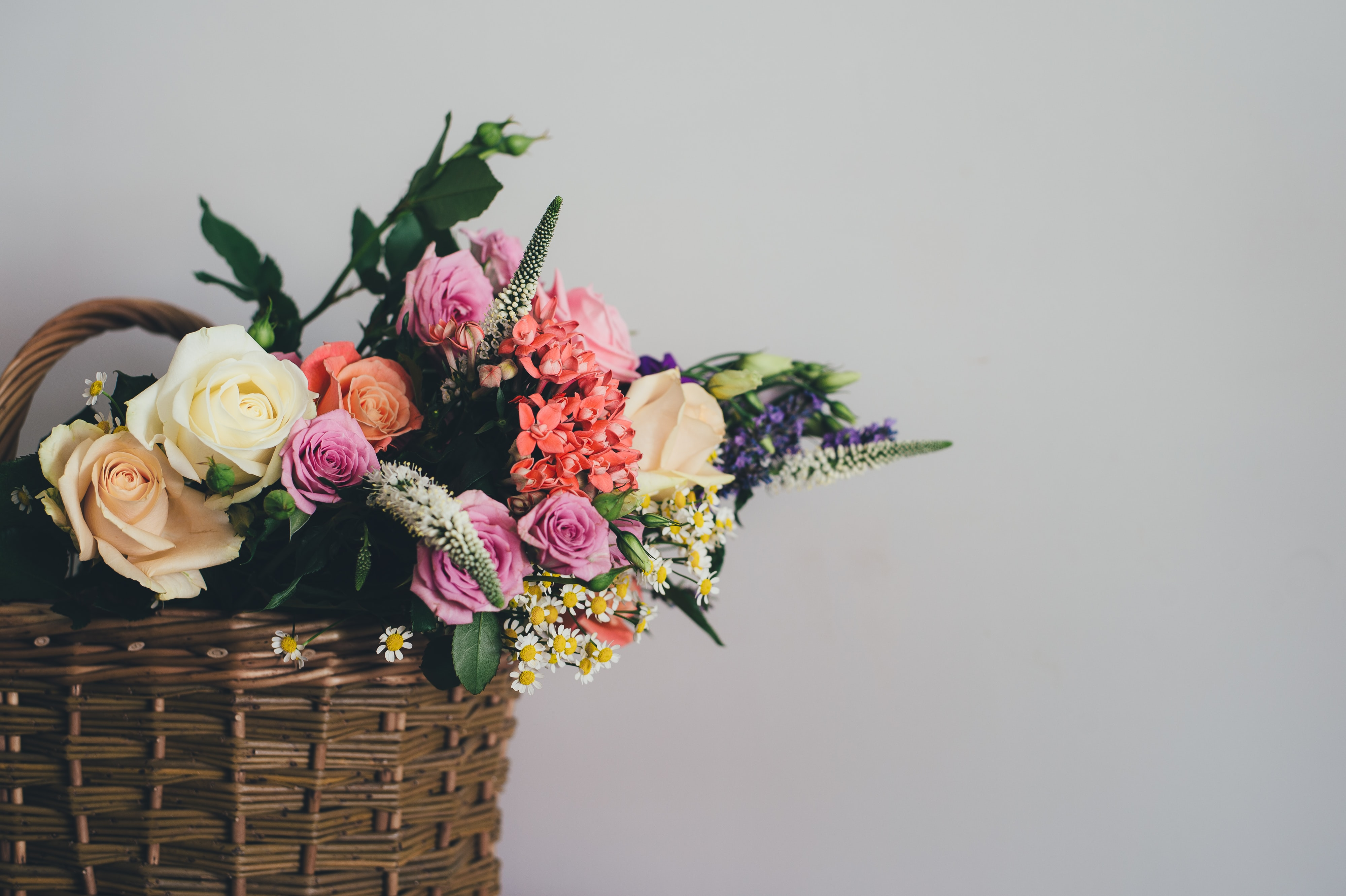 assorted-color flowers on brown wicker basket