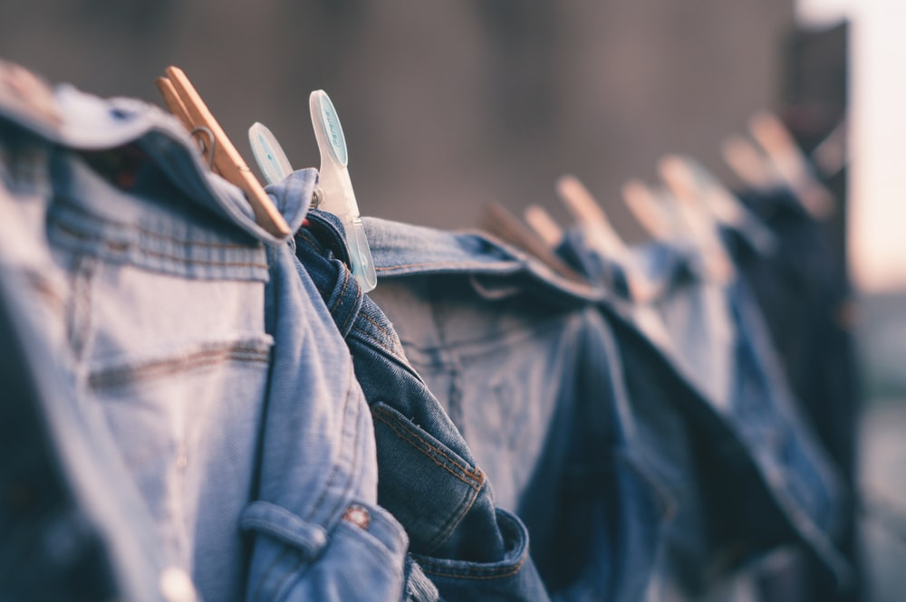 selective focus photo of blue denim jeans hanged
