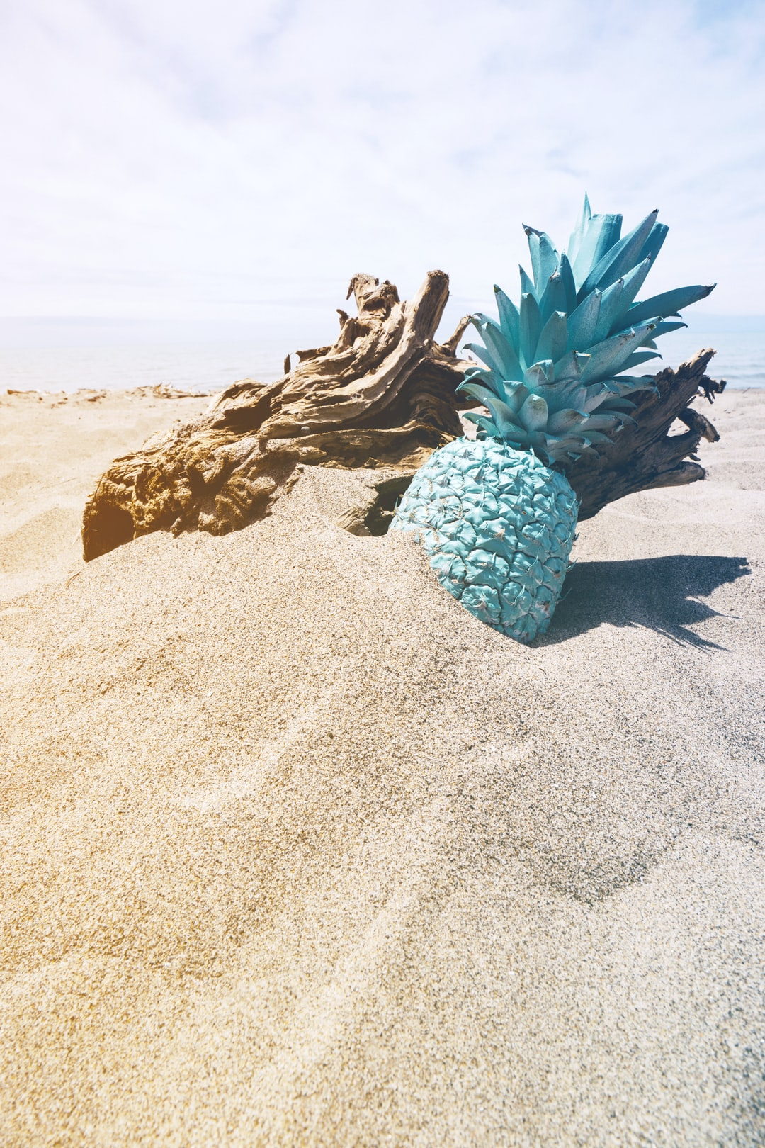 mint painted pineapple in sand at the beach
