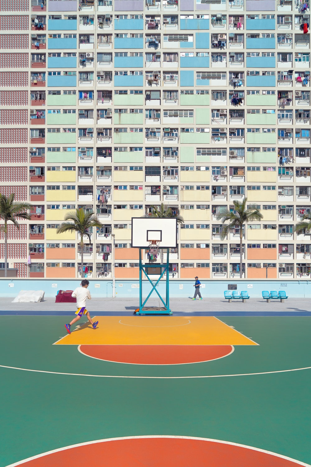 man running on basketball court during day time