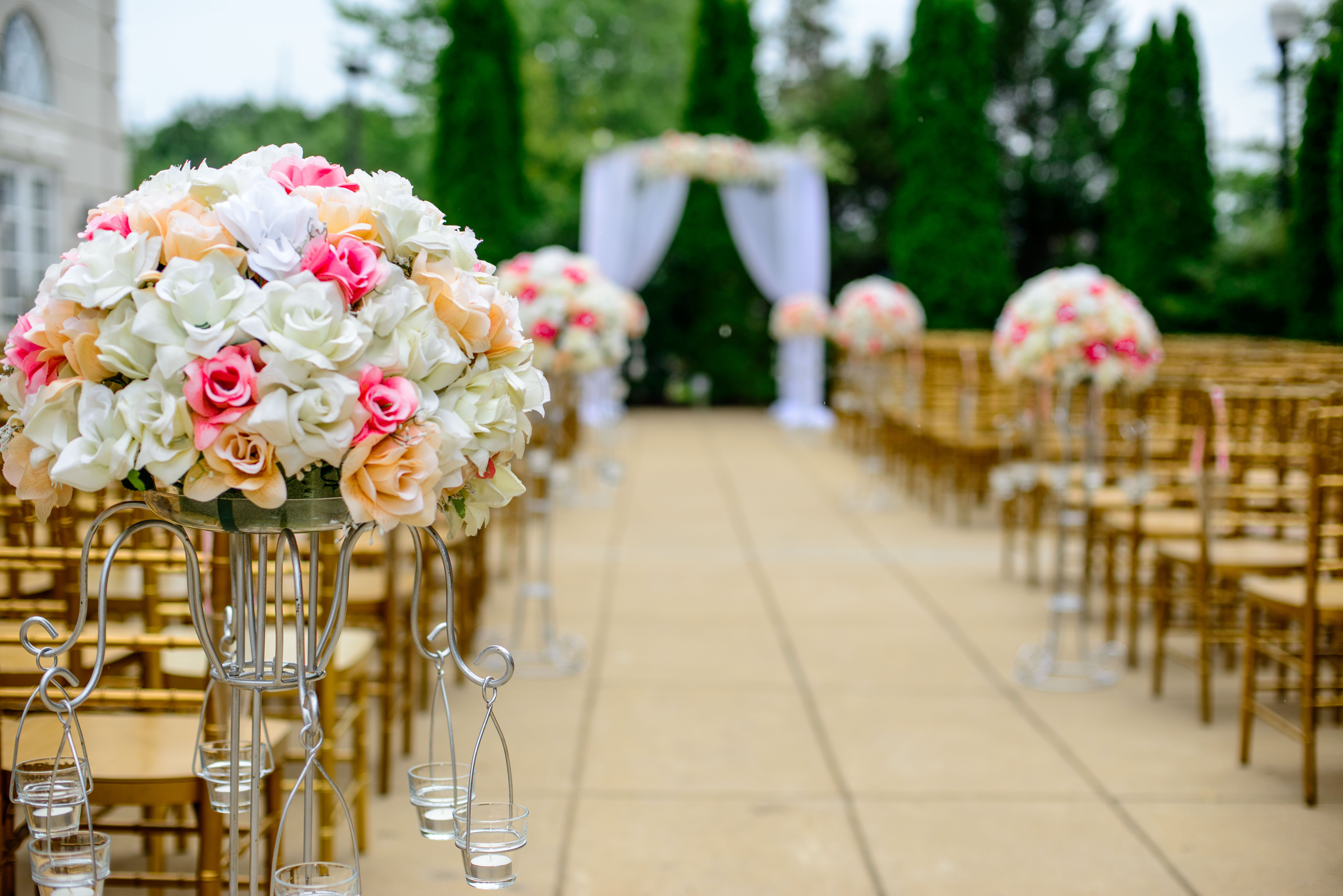 A scene prepared for a wedding with flower bouquets, empty chairs, and an altar