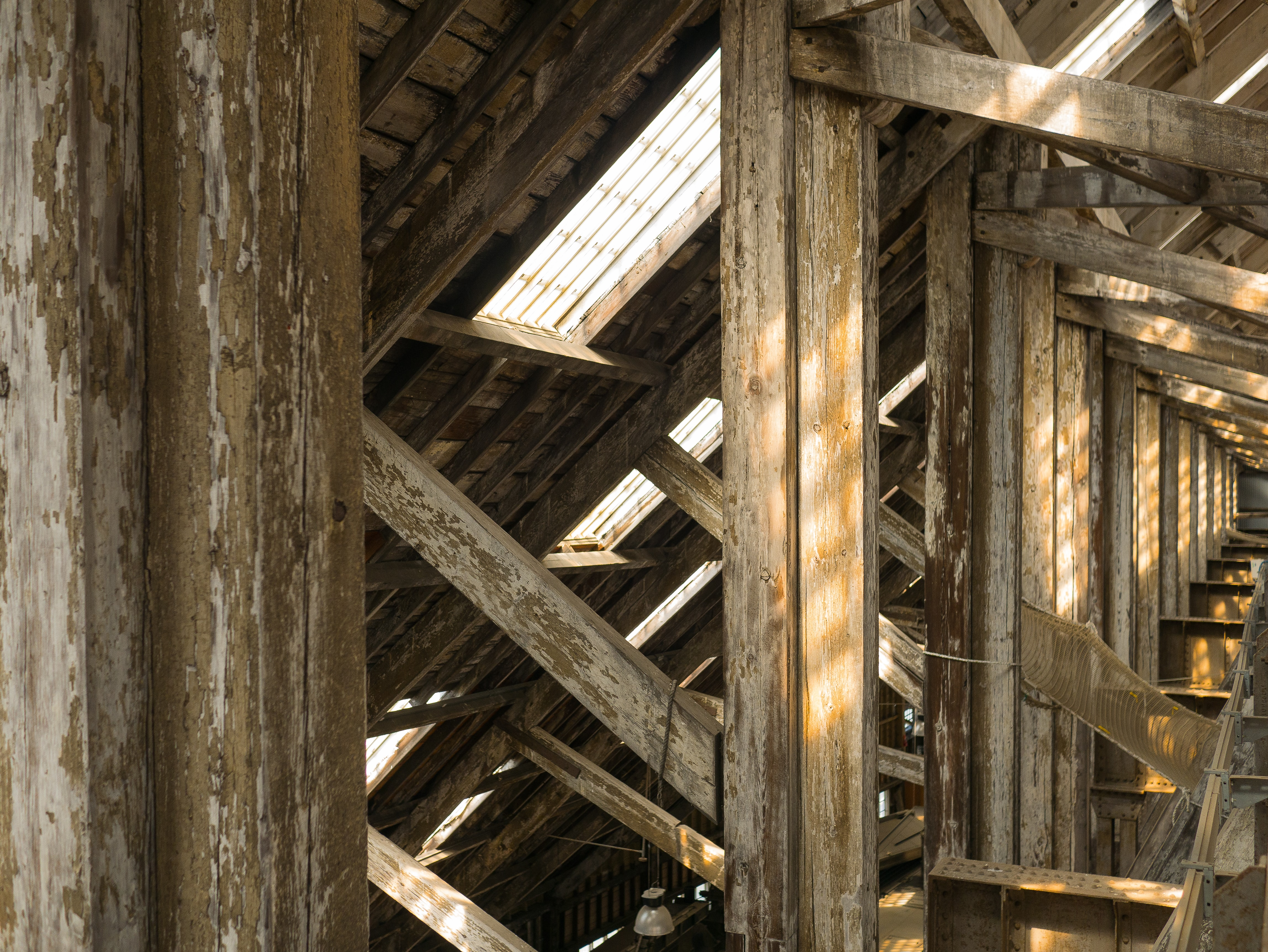 A number of beams under the ceiling of an old wooden building