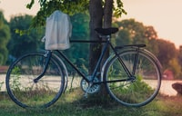 white cloth hanged on bike's handlebar leaned on tree