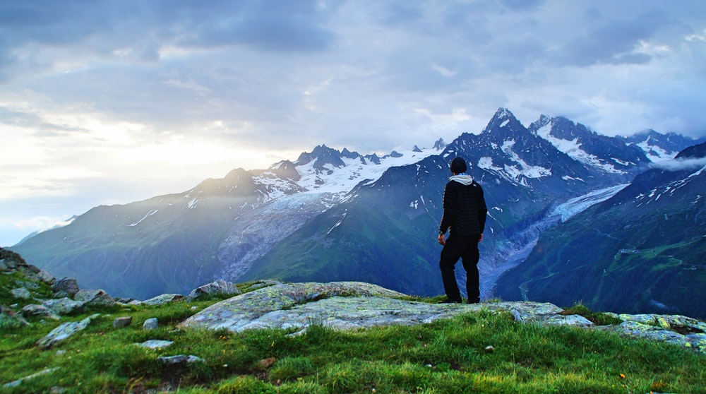 person standing in front of mountain landscape photography