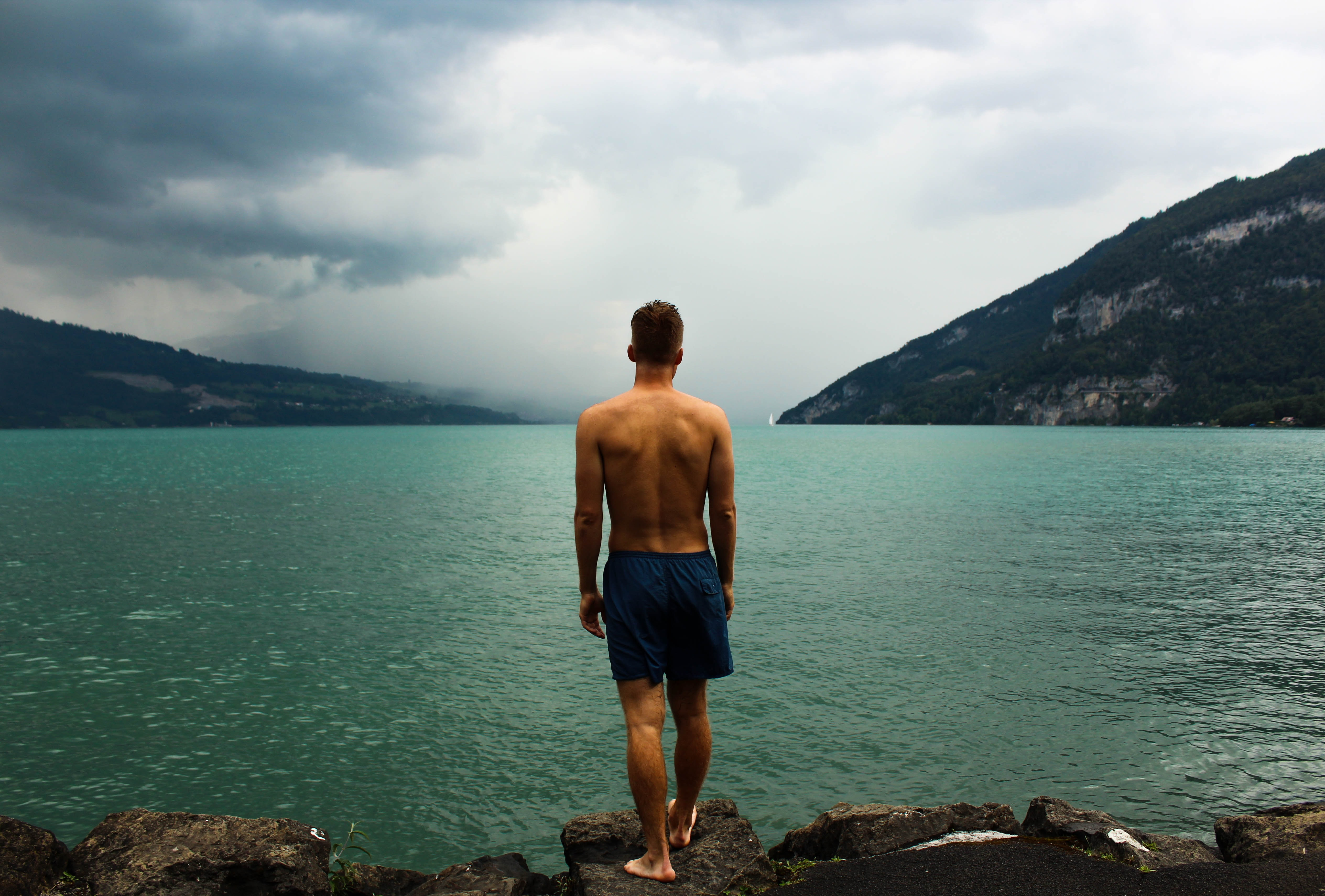 Man about to take a swim in a lake by rocky bluffs