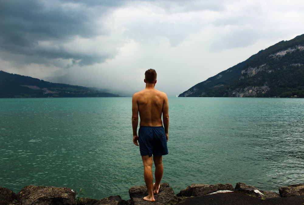 man wearing black shorts standing in front of body of water