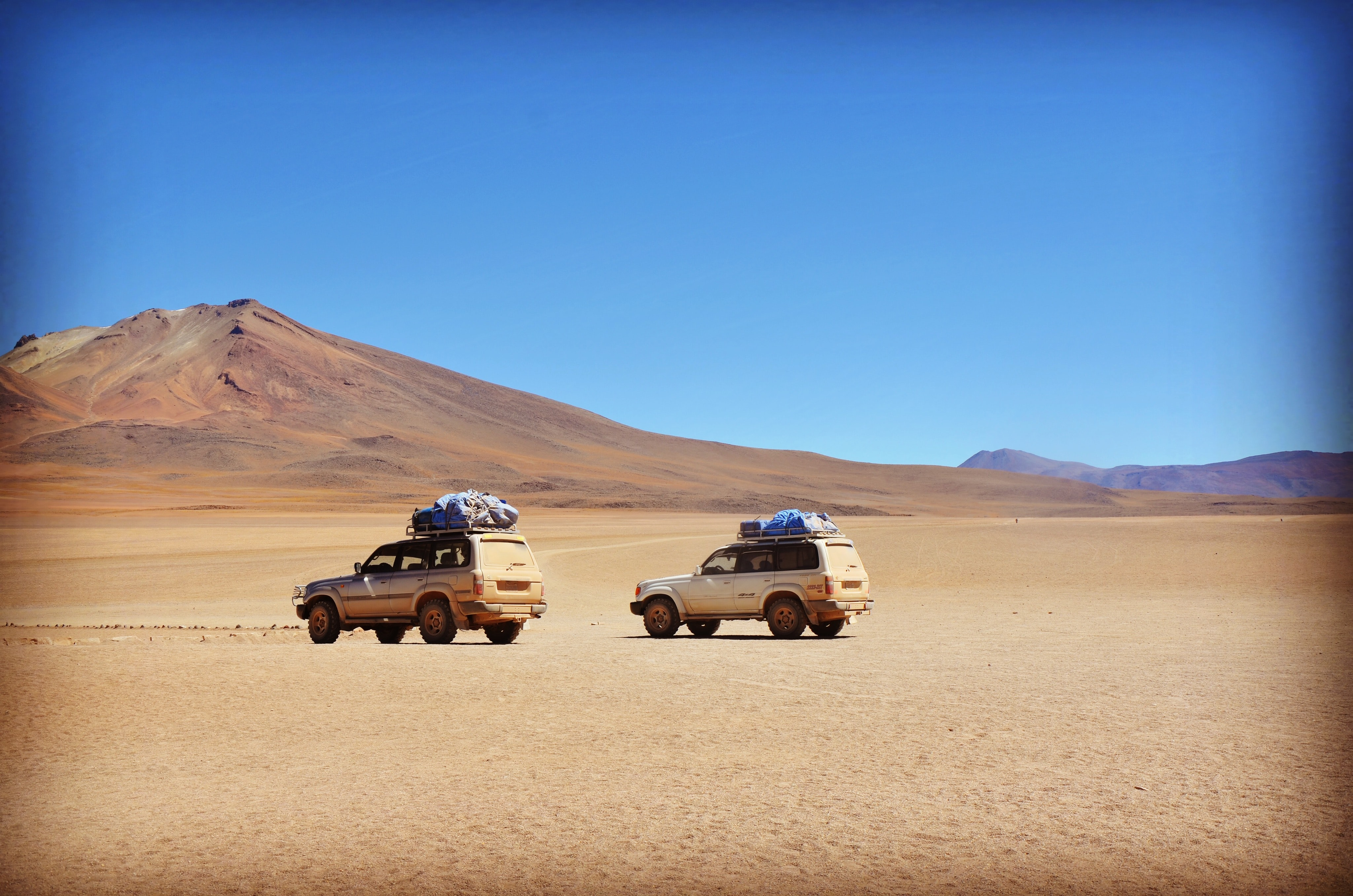 Two off-road vehicles in a mountain desert under clear sky