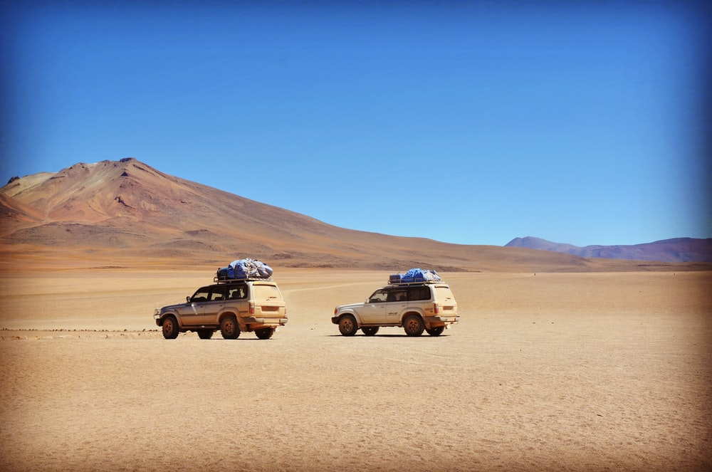 two grey SUV's on grey desert