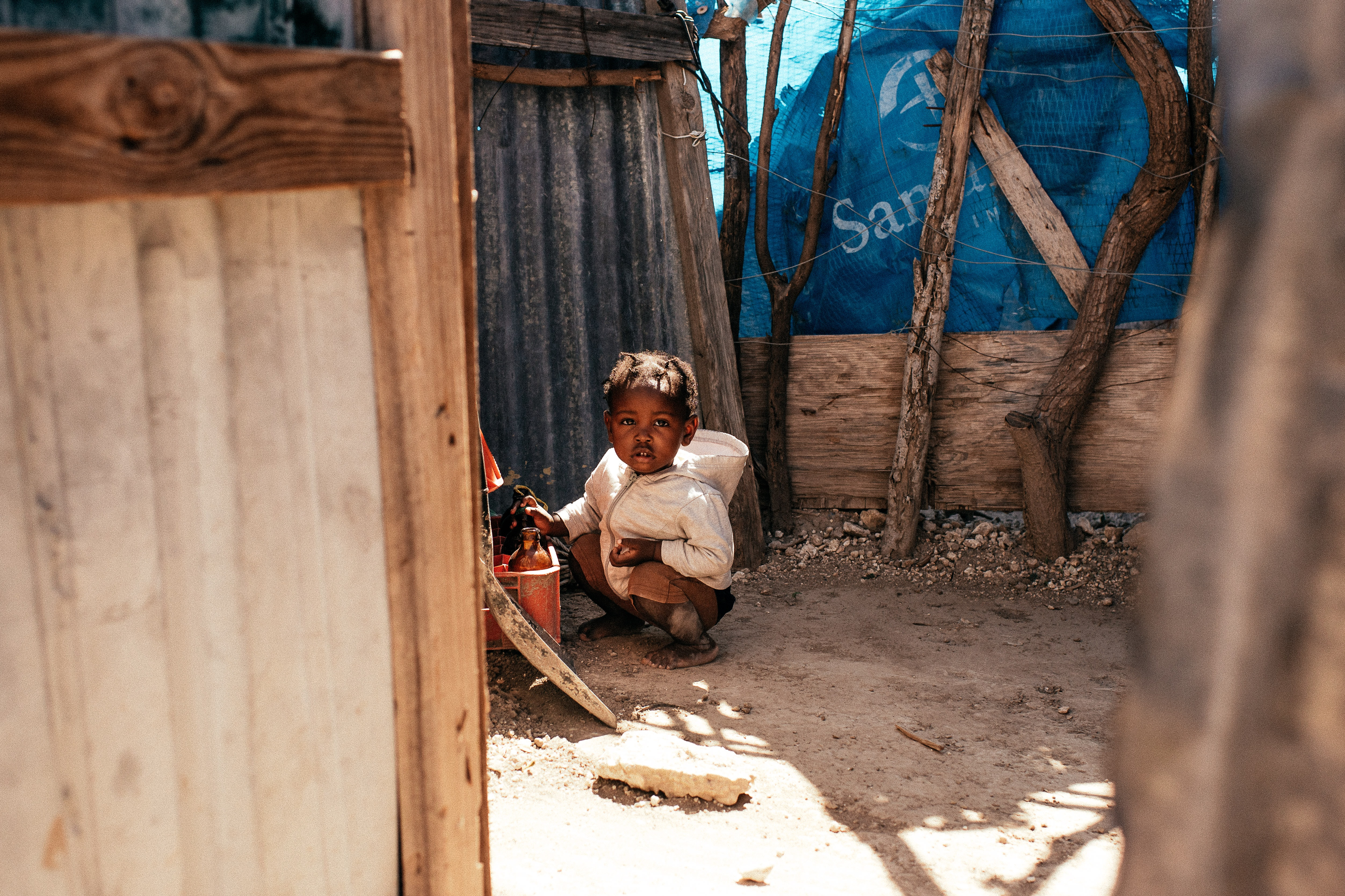 A child wearing a white coat squats on the ground in the dirt to touch some bottles near a building.