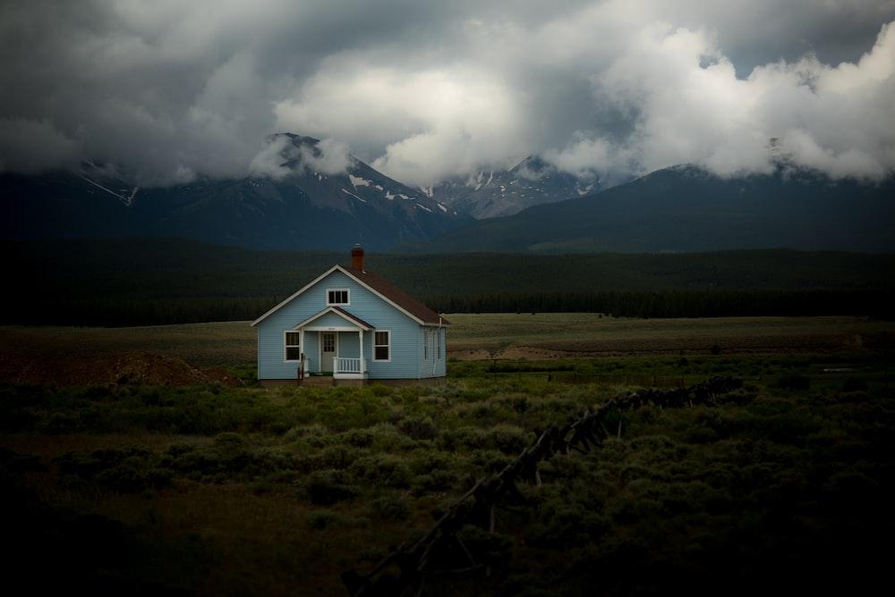 house on grass field under gray sky