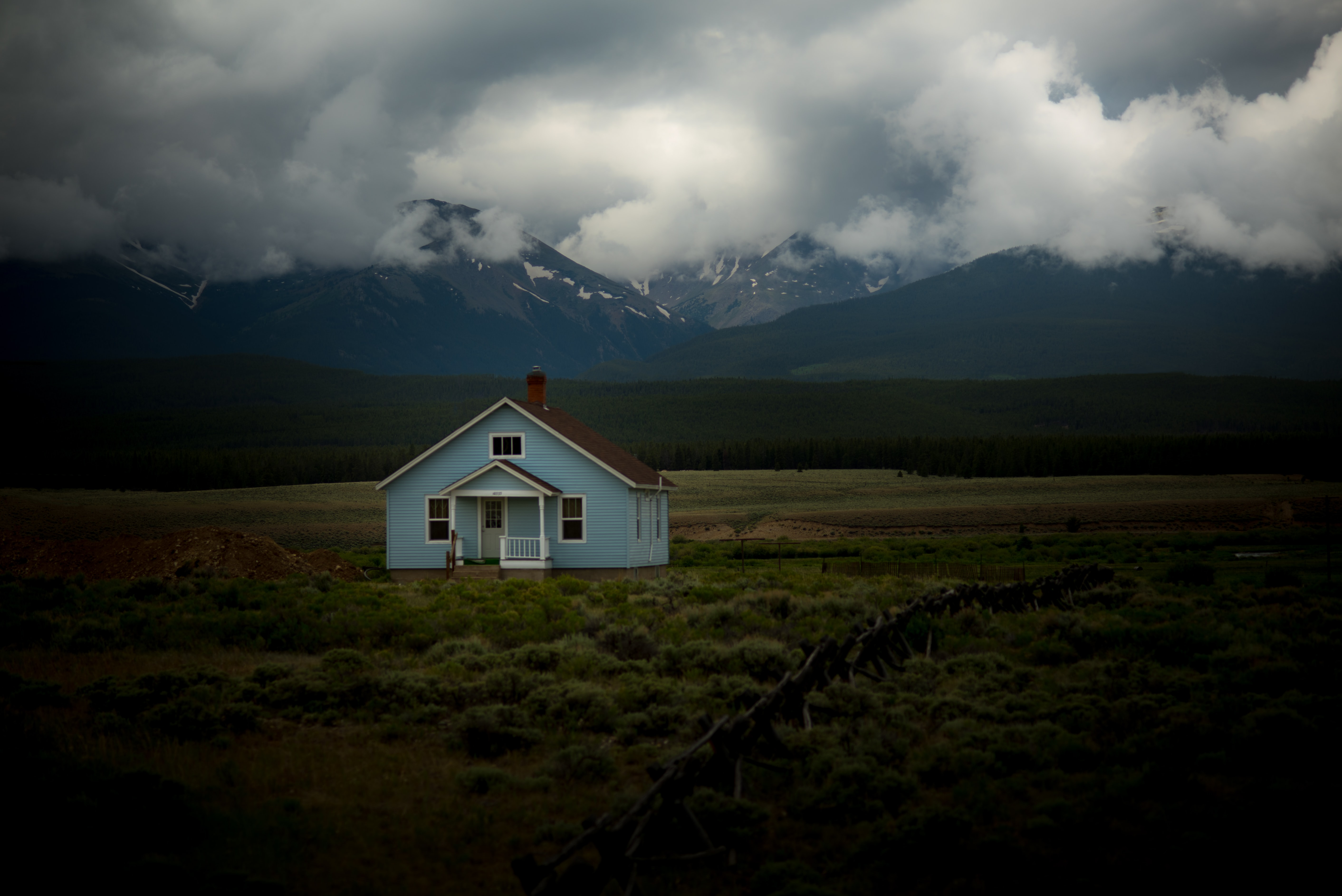 Small, blue house in the middle of a field of grass with mountains covered in clouds behind it