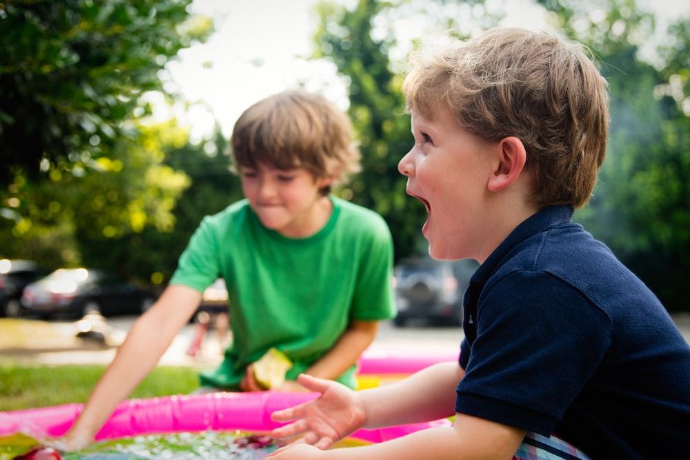 boy in blue shirt screaming near boy in green crew-neck shirt
