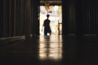 silhouette of person standing beside wall