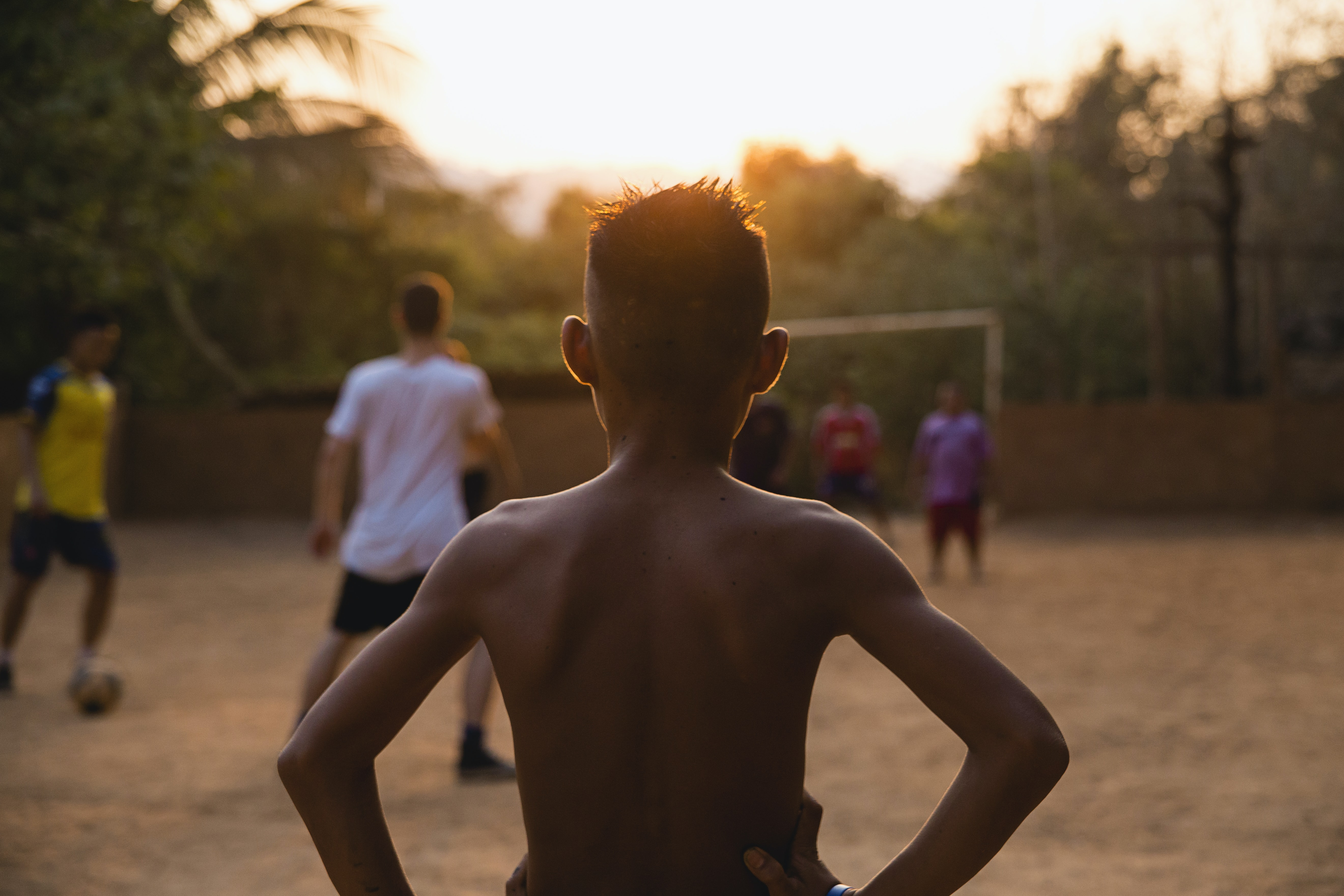 A shirtless African American boy watching a soccer game.