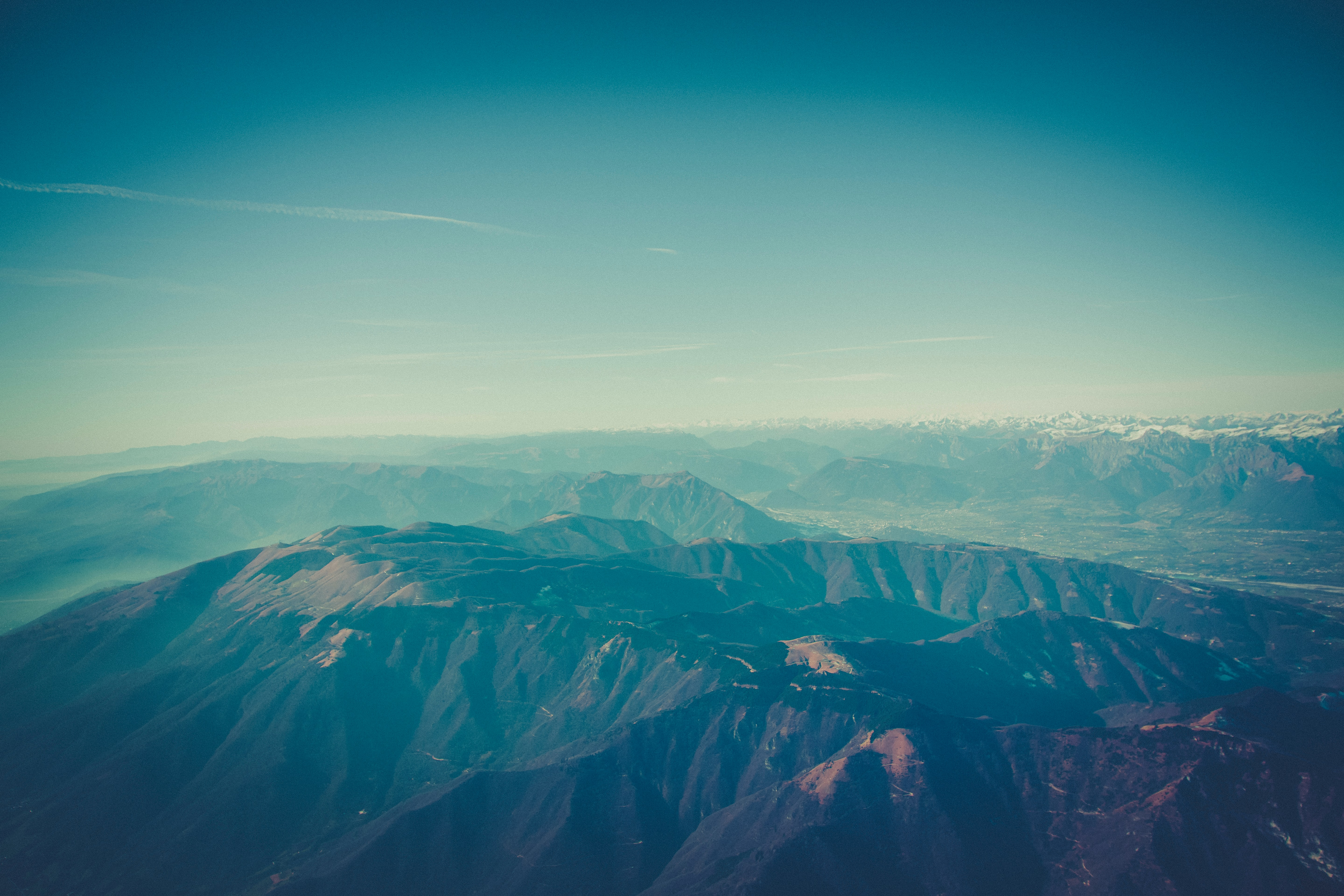 An aerial shot of an expanse of hazy blue mountains