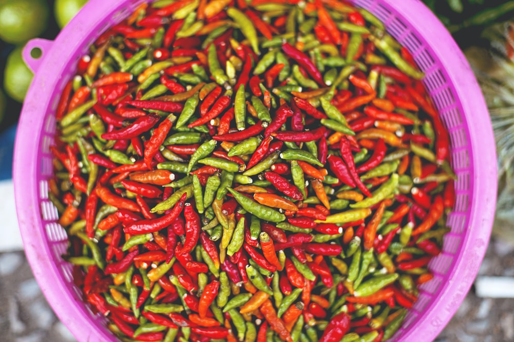 green and red chili lot on pink strainer