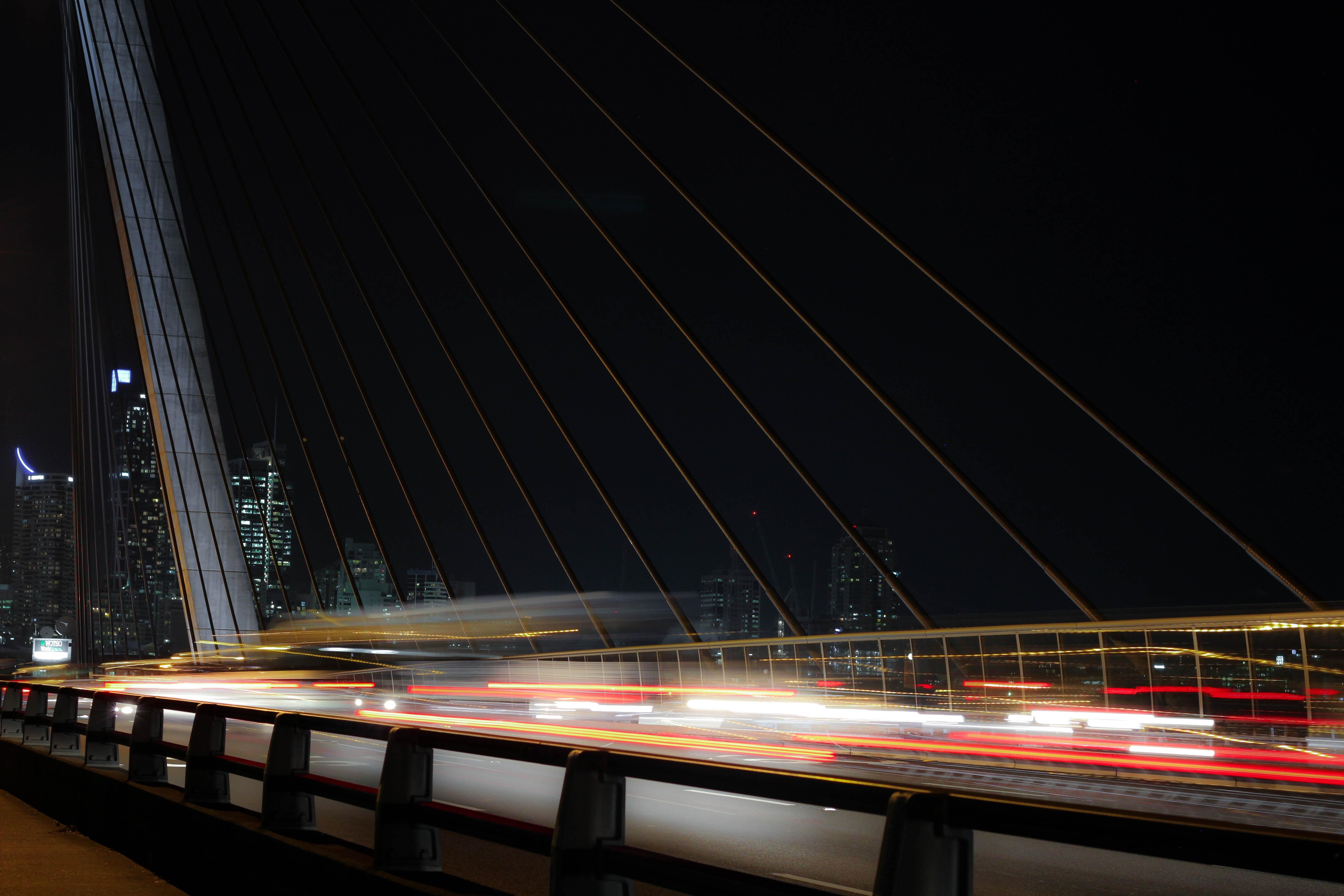 A dark and blurry shot of traffic light trails on a tension bridge in Sydney