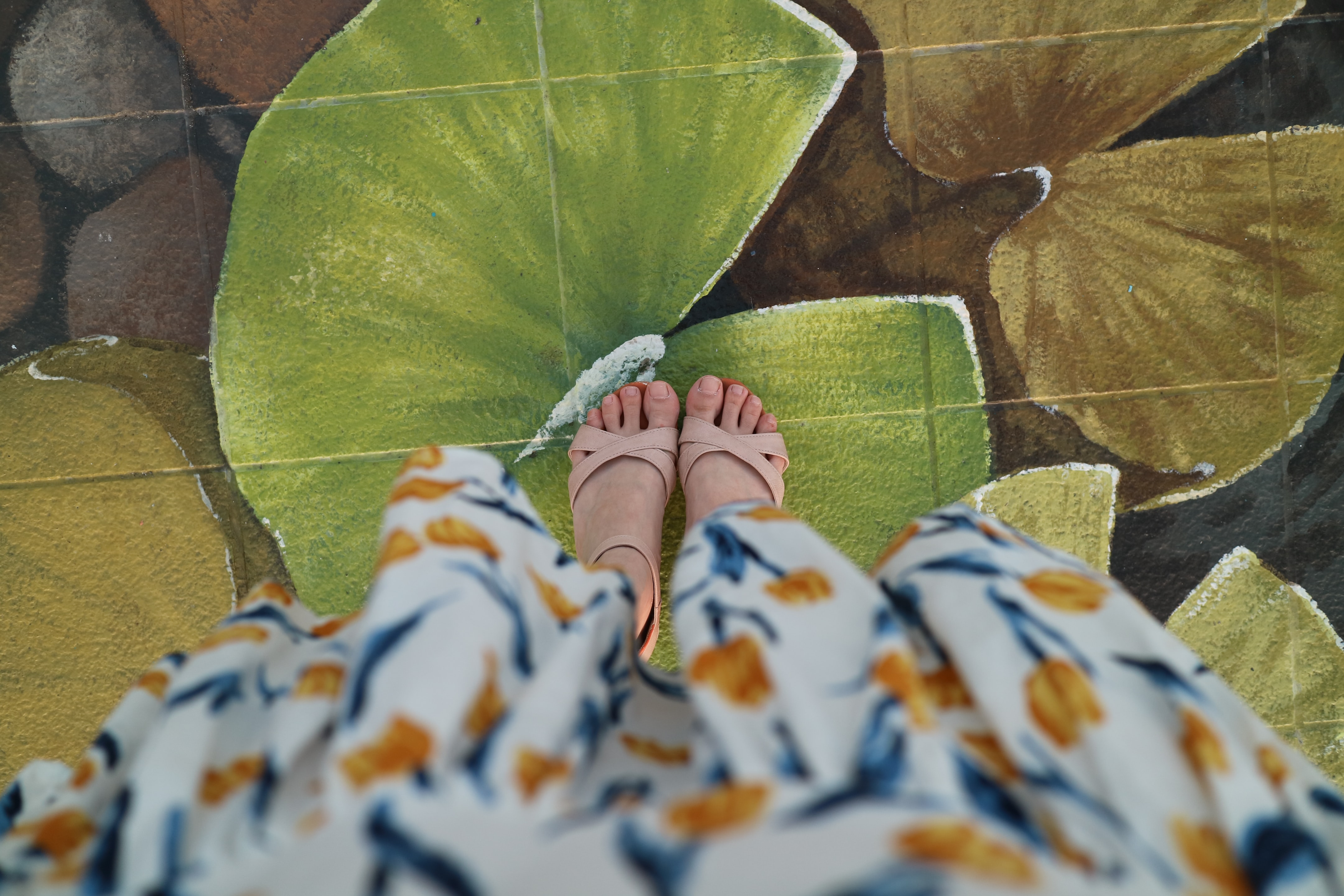Woman in floral dress and sandals' feet standing on green water lily street art, Busan