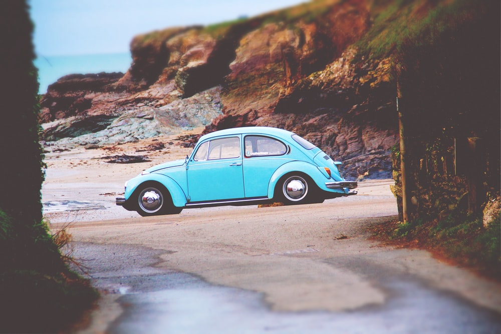 teal Volkswagen Beetle on seashore