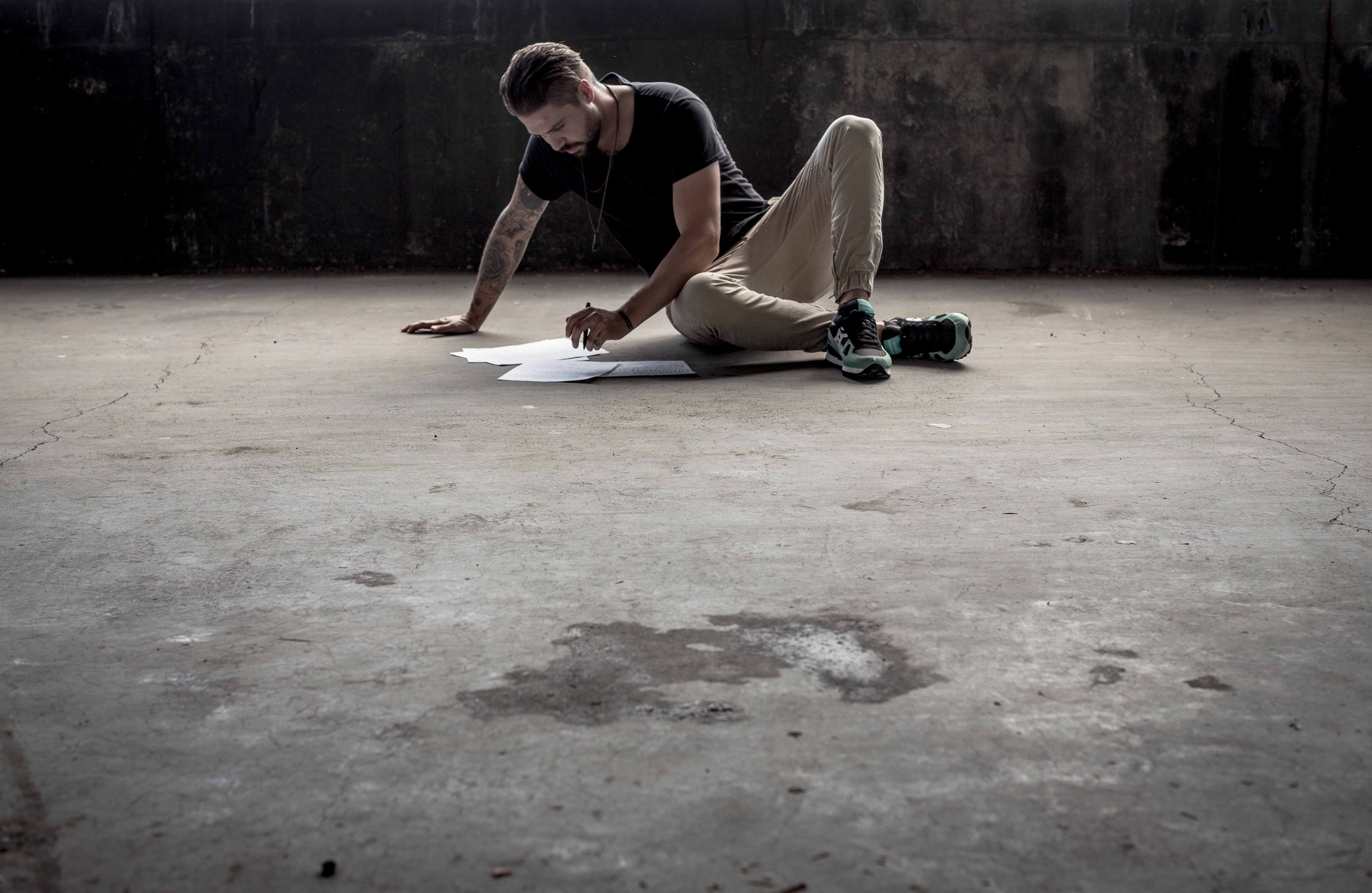 A man with a pen looking at sheets of paper while seated on a concrete industrial floor