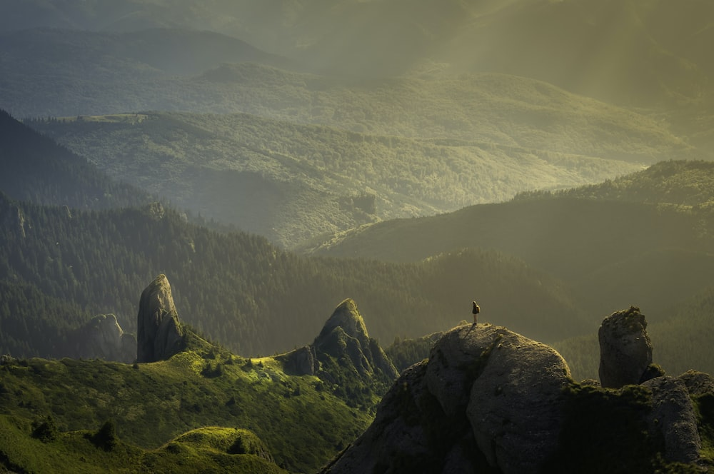 A Person Standing On Rock Overlooking Sun Drenched Undulating Valley