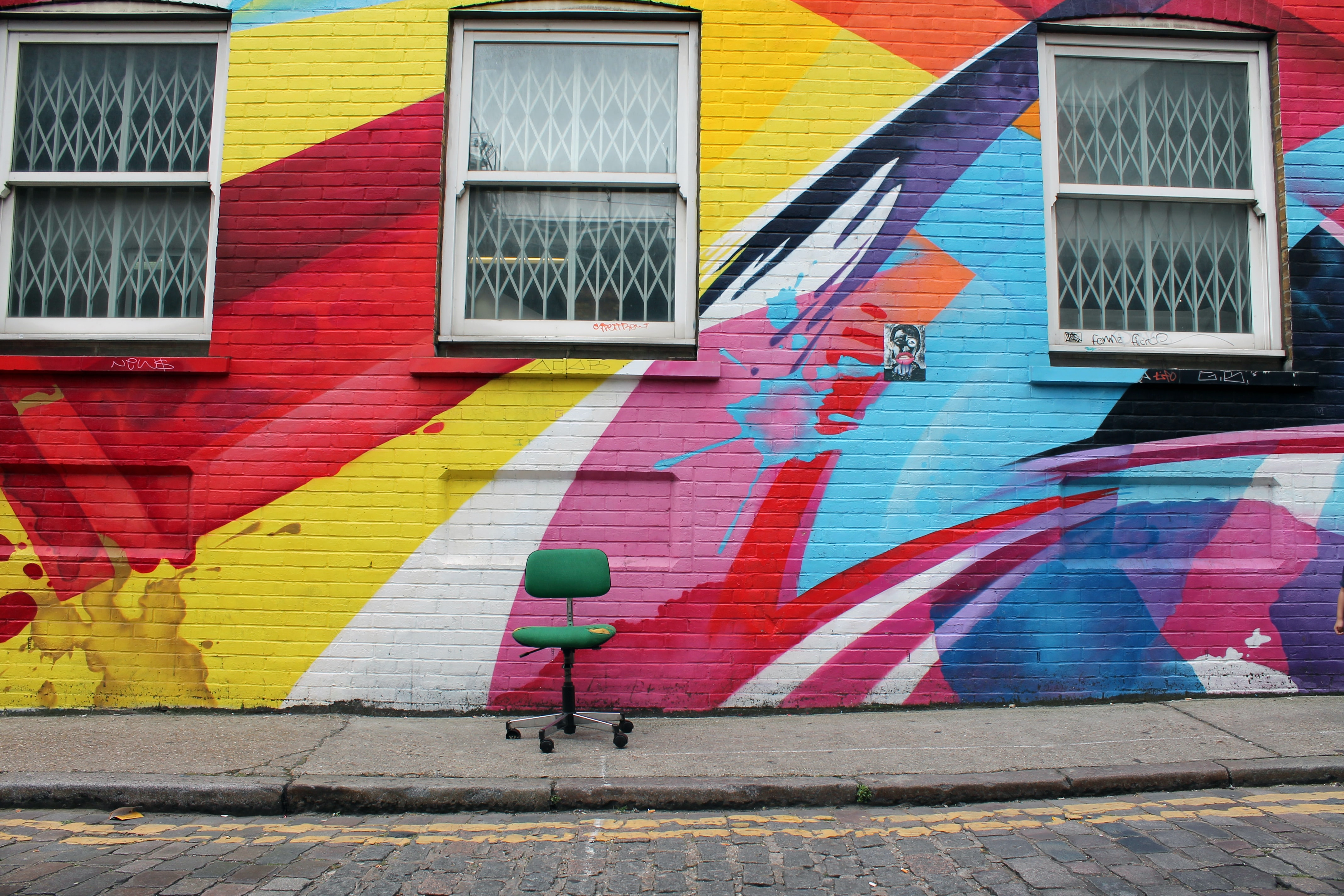 Green chair sits in front of colorful graffiti on brick building with three windows