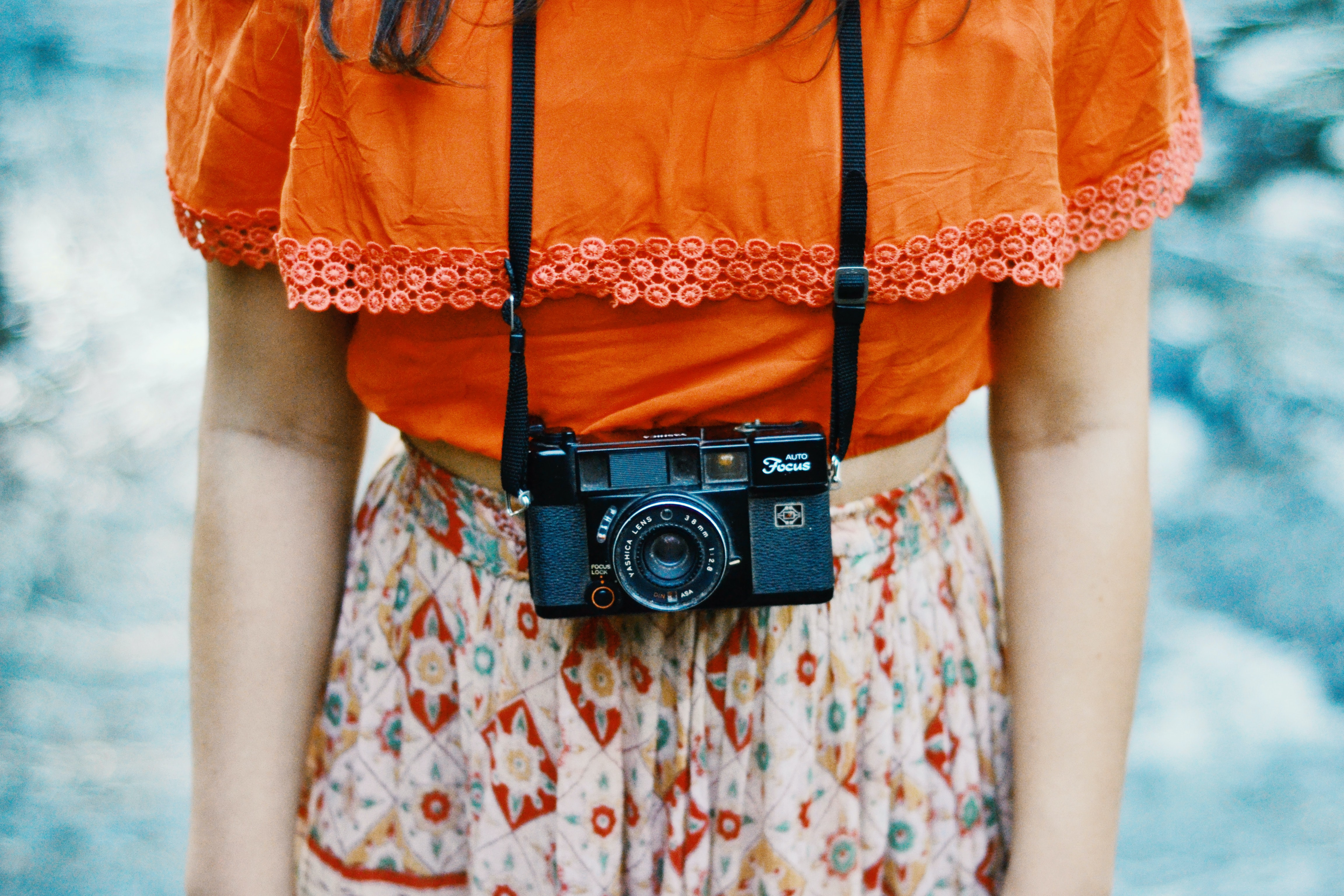 woman wearing orange and multicolored dress with black bridge camera on her neck
