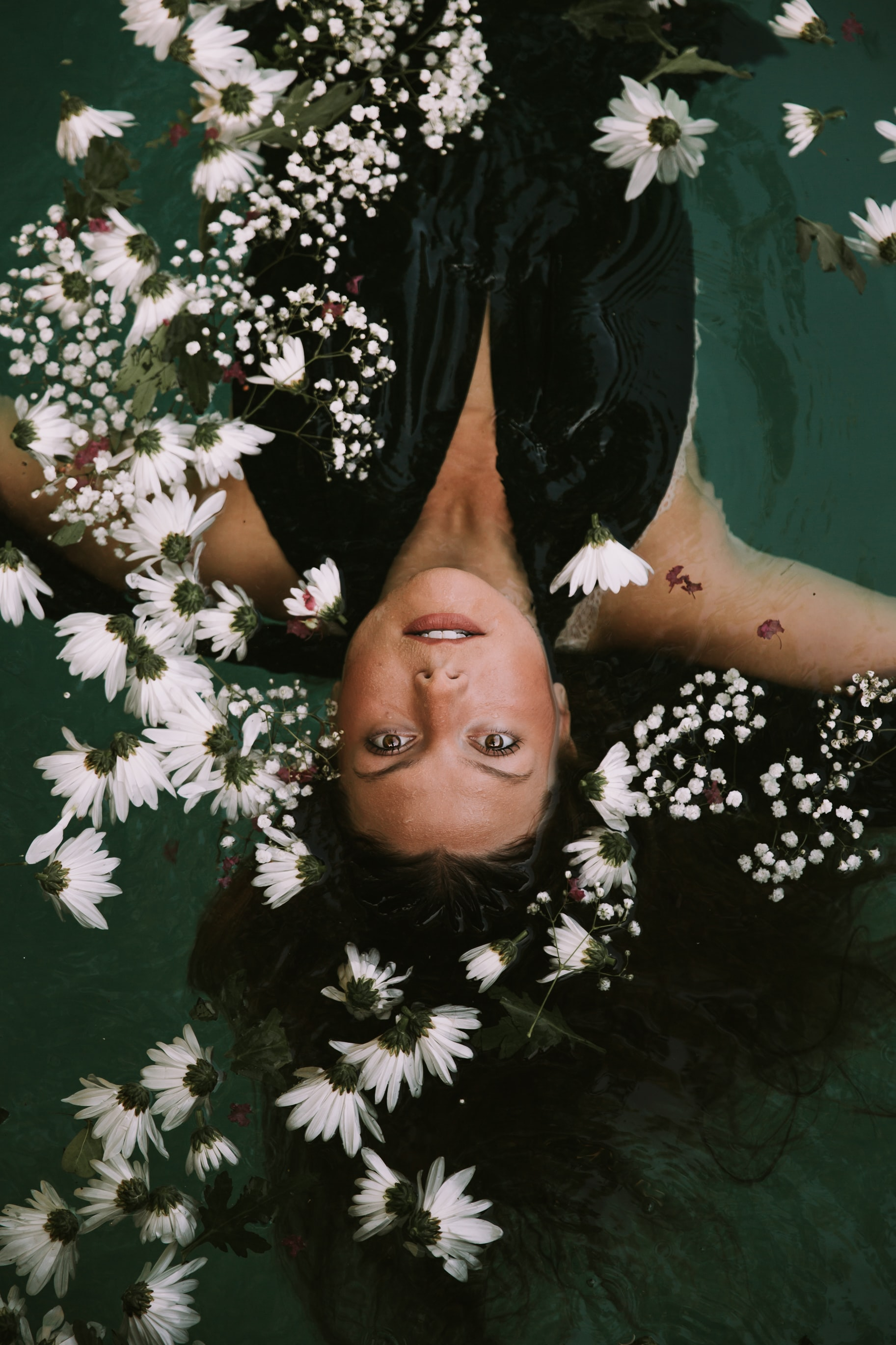 woman swimming covered by white daisies