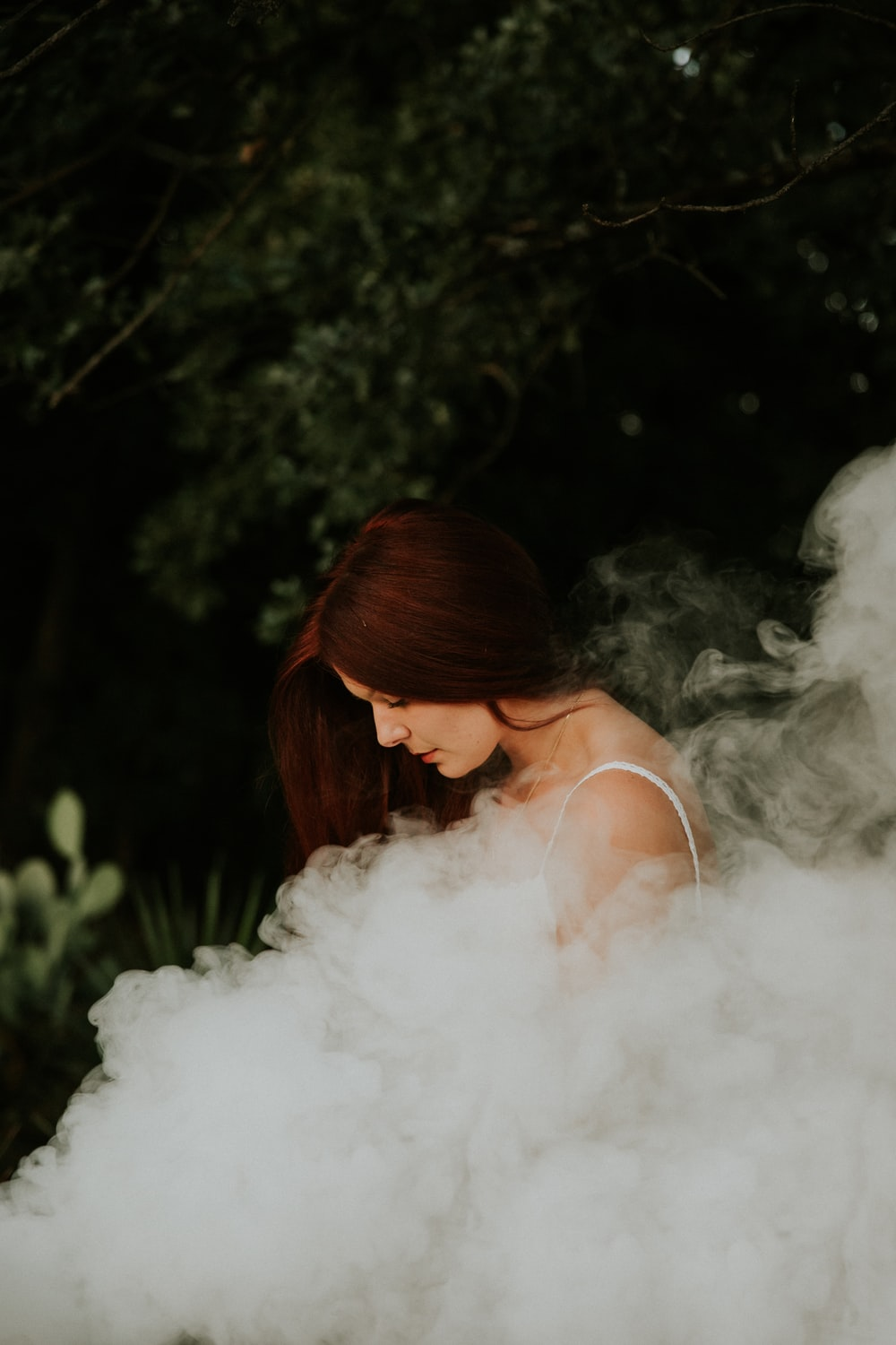 woman in white spaghetti strap sleeveless shirt standing near trees covered her body of smoke