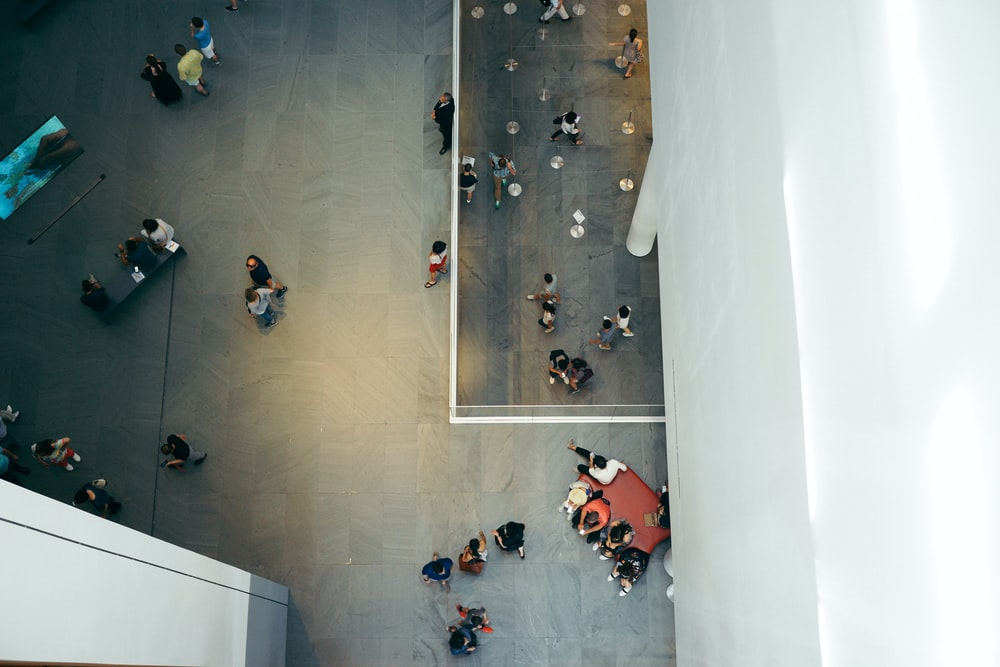 top-view photography of people beside white concrete building