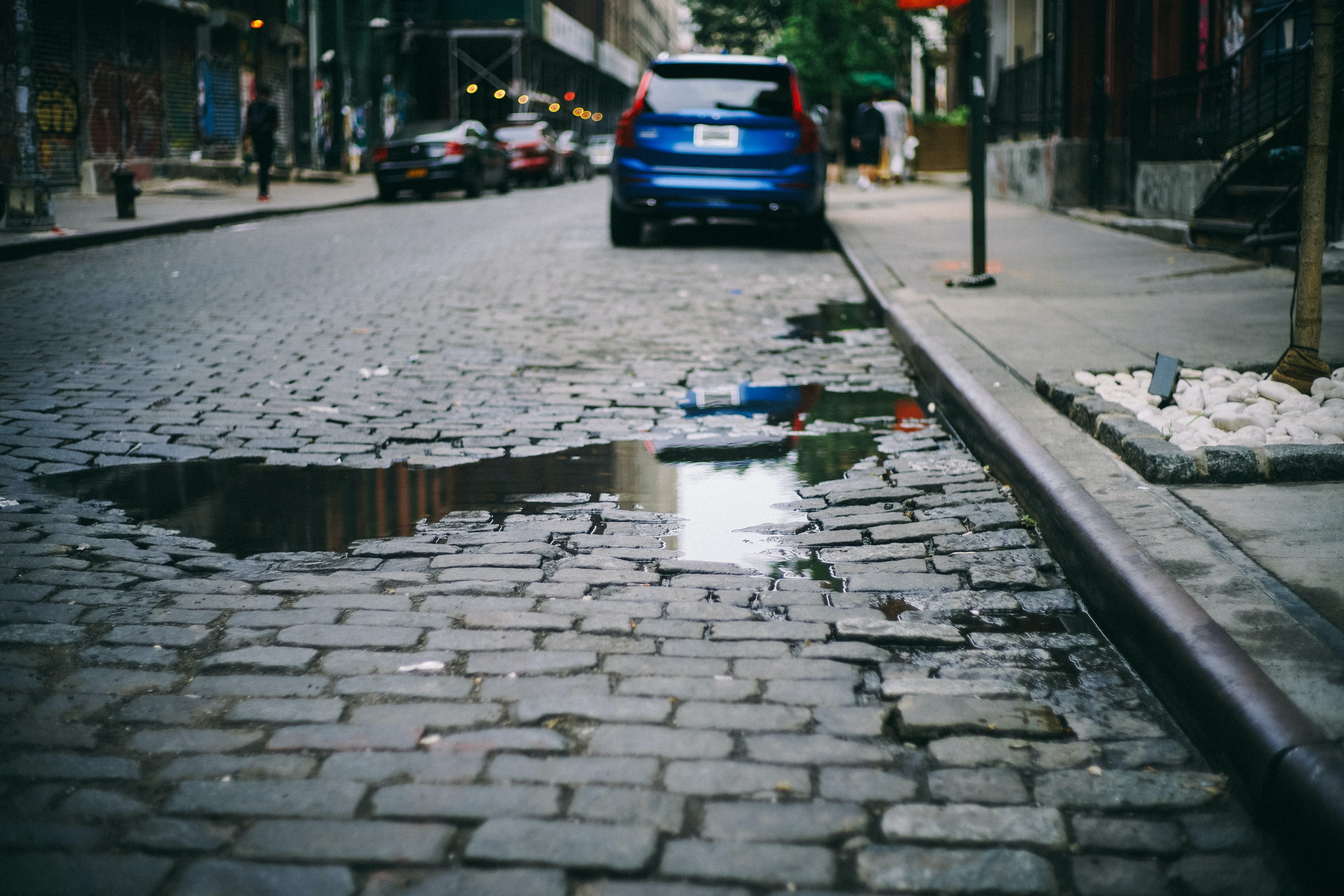 Cobblestone street with parked car and puddle reflecting sky