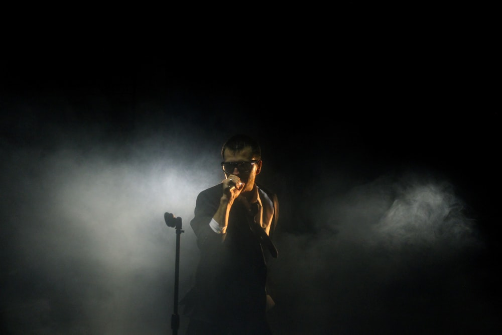 man standing beside microphone stand holding microphone
