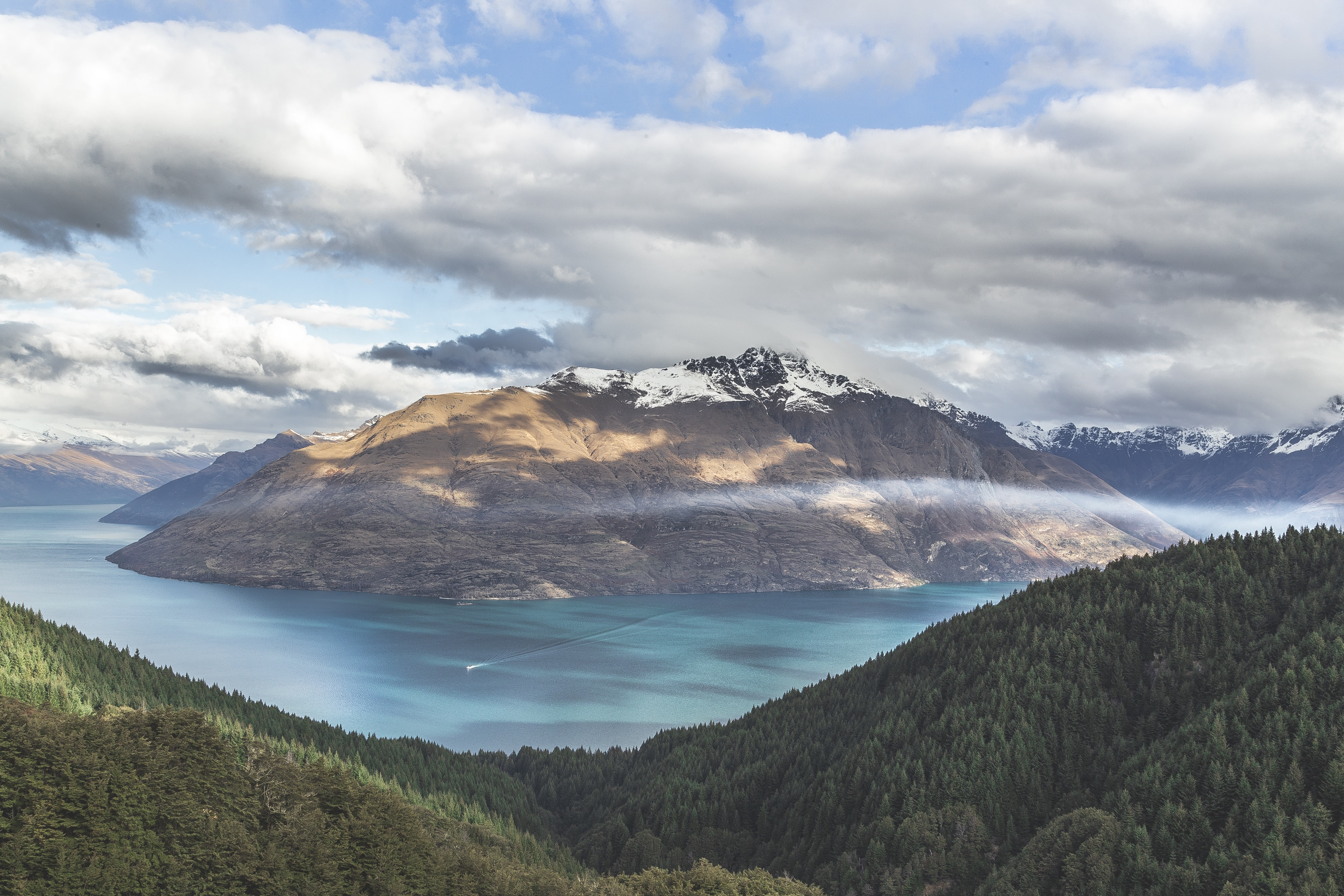 A large azure lake amid snow-capped mountains and wooded hills