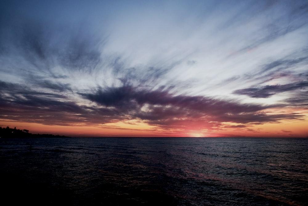 ocean under gloomy sky during golden hour