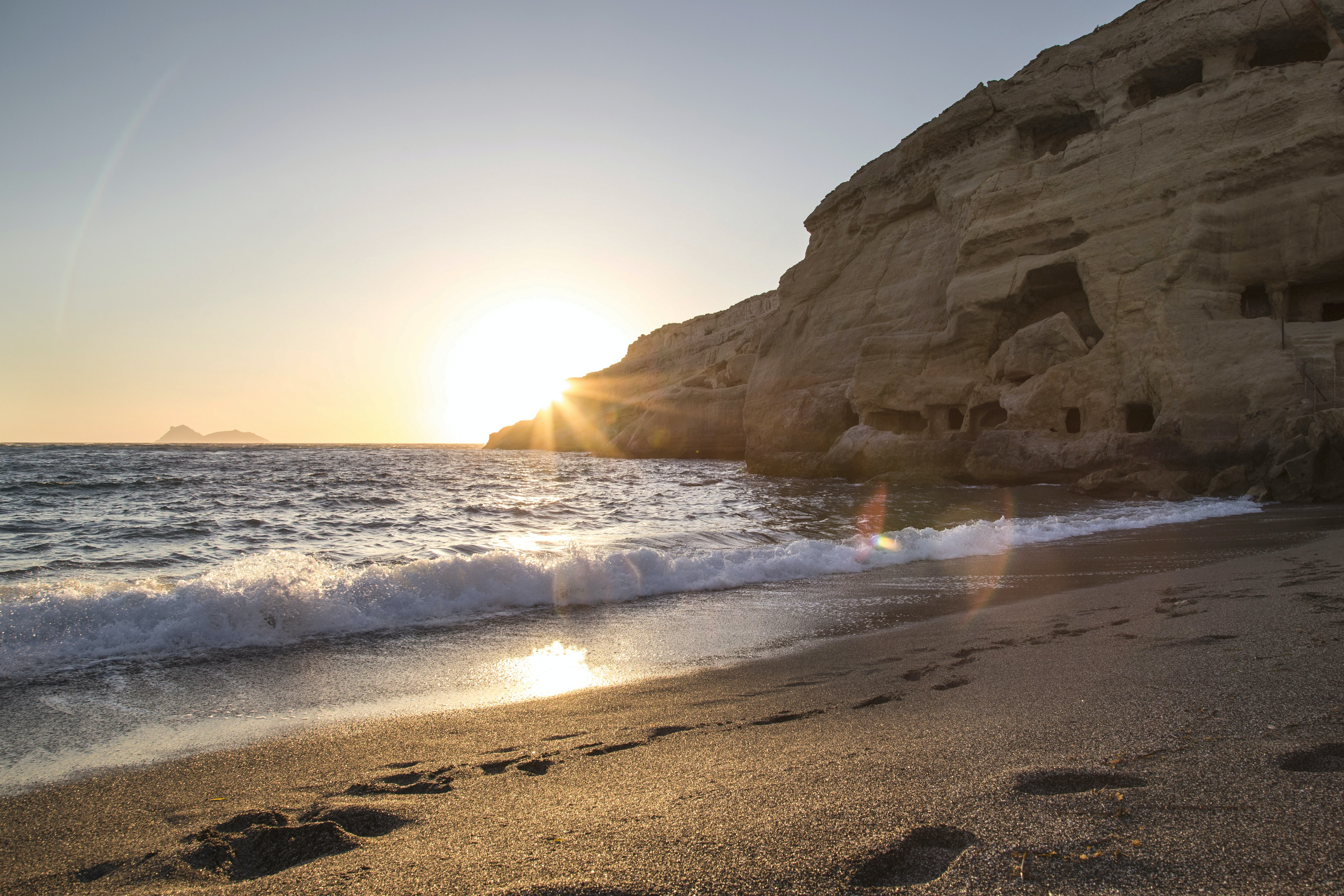 A course sand beach in Matala, with foot marks along the shoreline leading toward a large rock coastline. Small waves crash into shore and the bright sunrise-or-sunset creates a yellow glare in the clear, pale blue sky