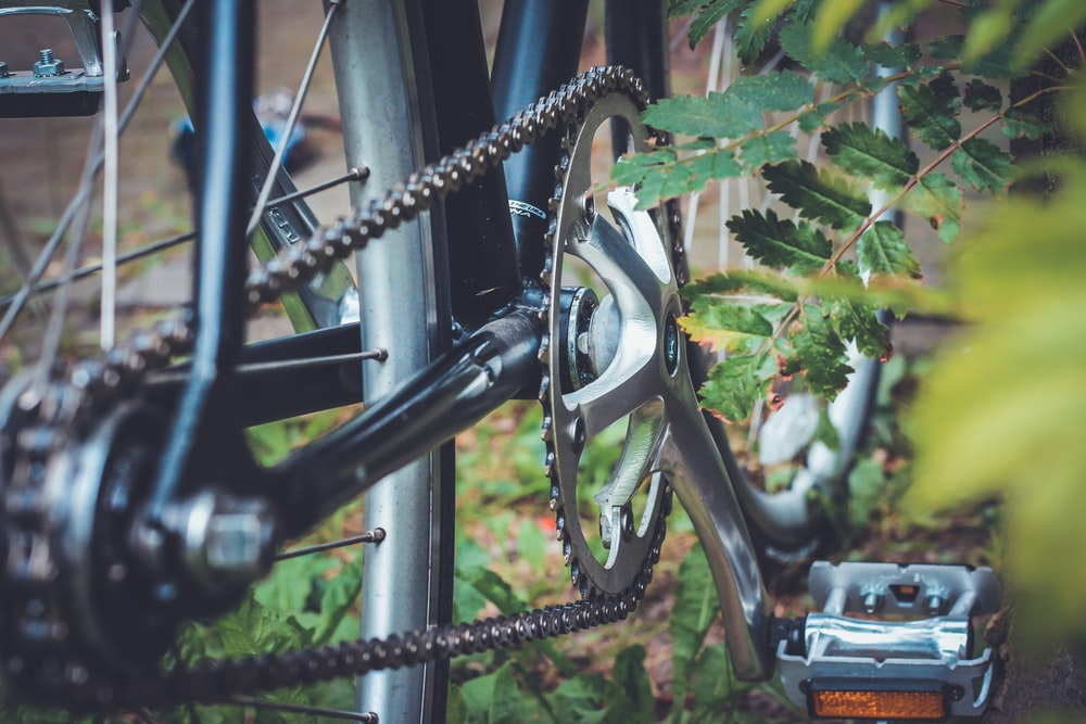 selective focus photo of bicycle derailleur and sprocket
