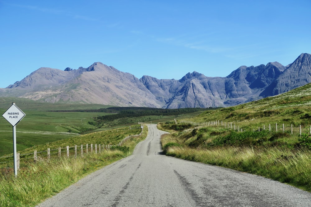 gray road with green fields far at the mountains during daytime photography