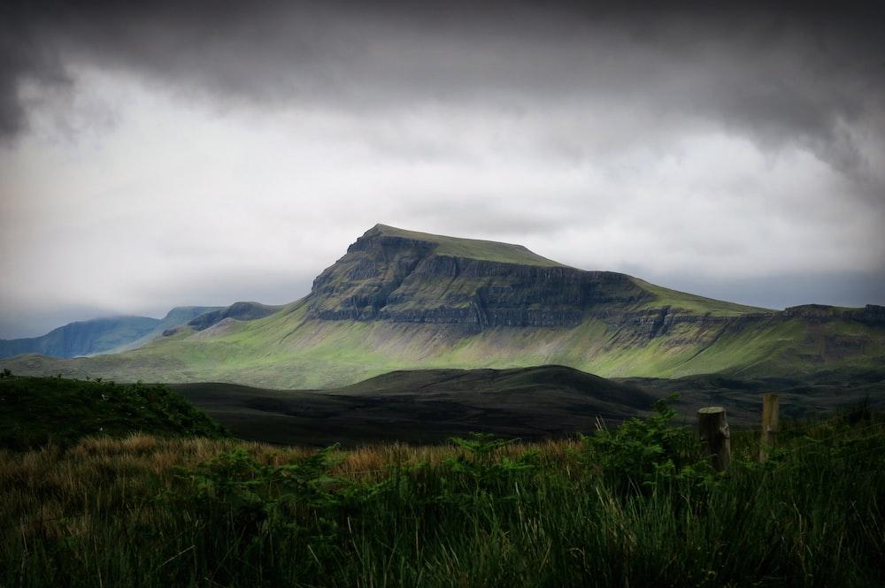 green mountain under cloudy sky ]
