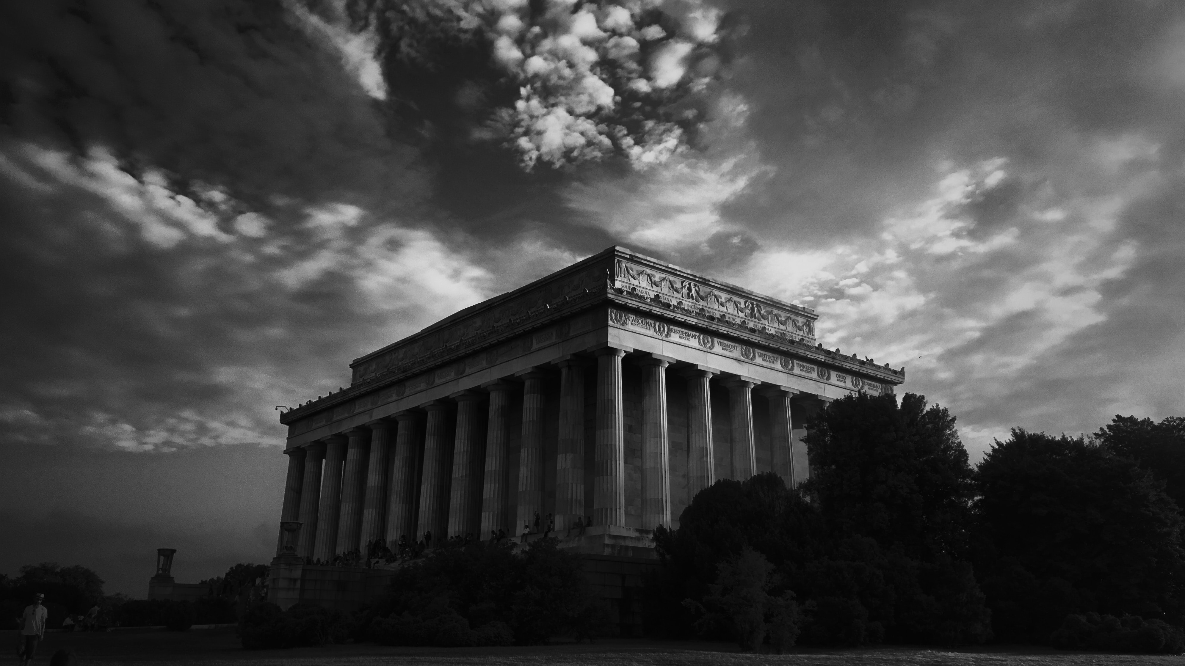 Black and white long shot of classic ancient building with pillars, cloudy sky and trees